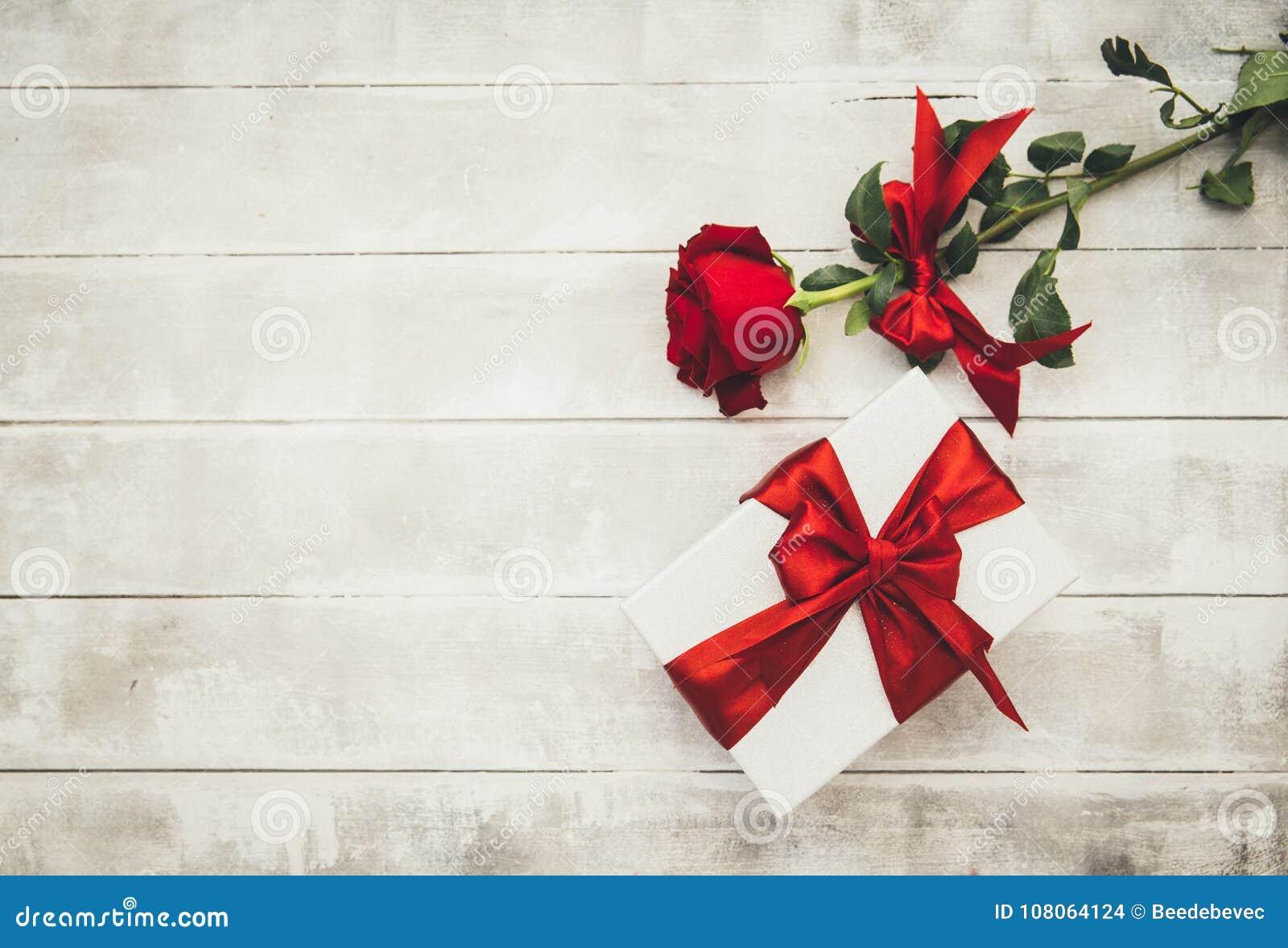 Rood rozen en giftvakje op een houten lijst Gelukkige valentijnskaartendag