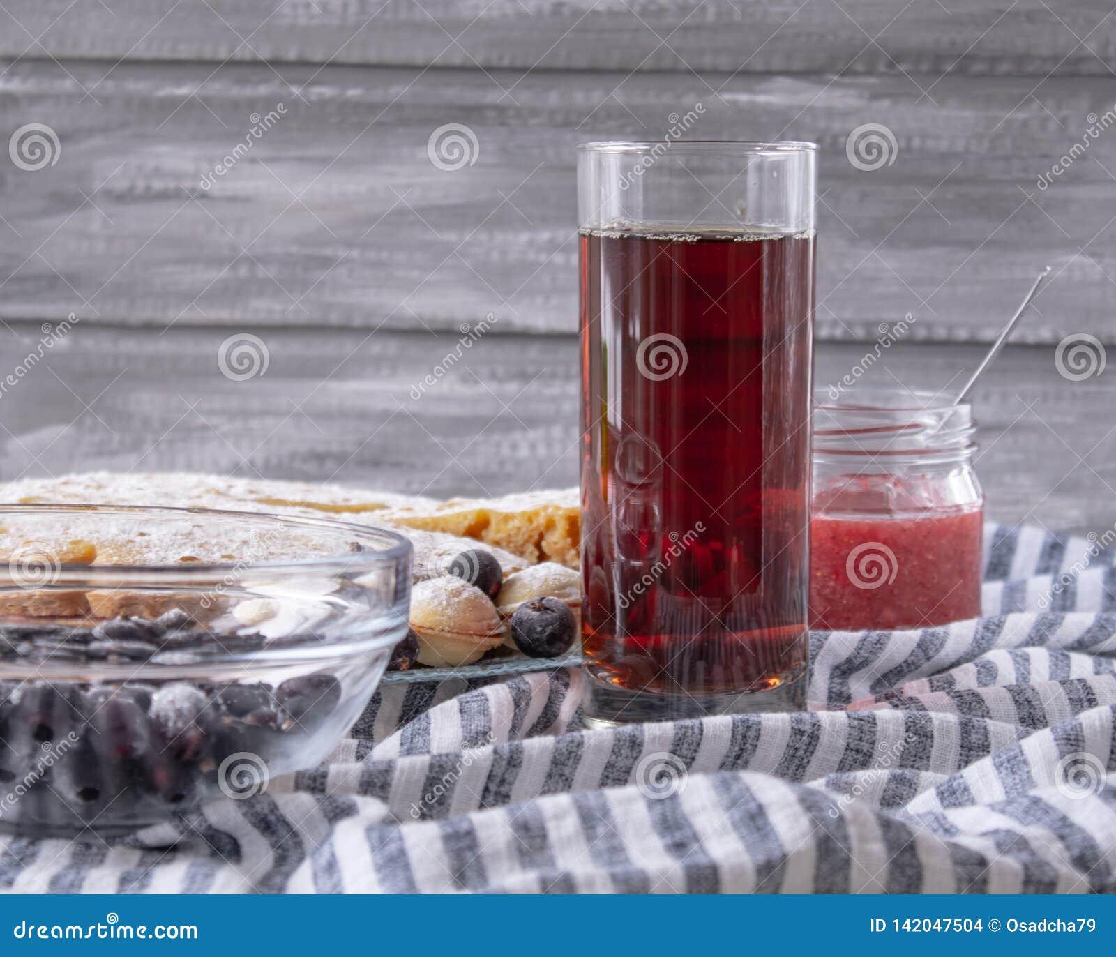 Rood sap in een glas naast een kom van koekjes en een kruik jam, op een grijze achtergrond