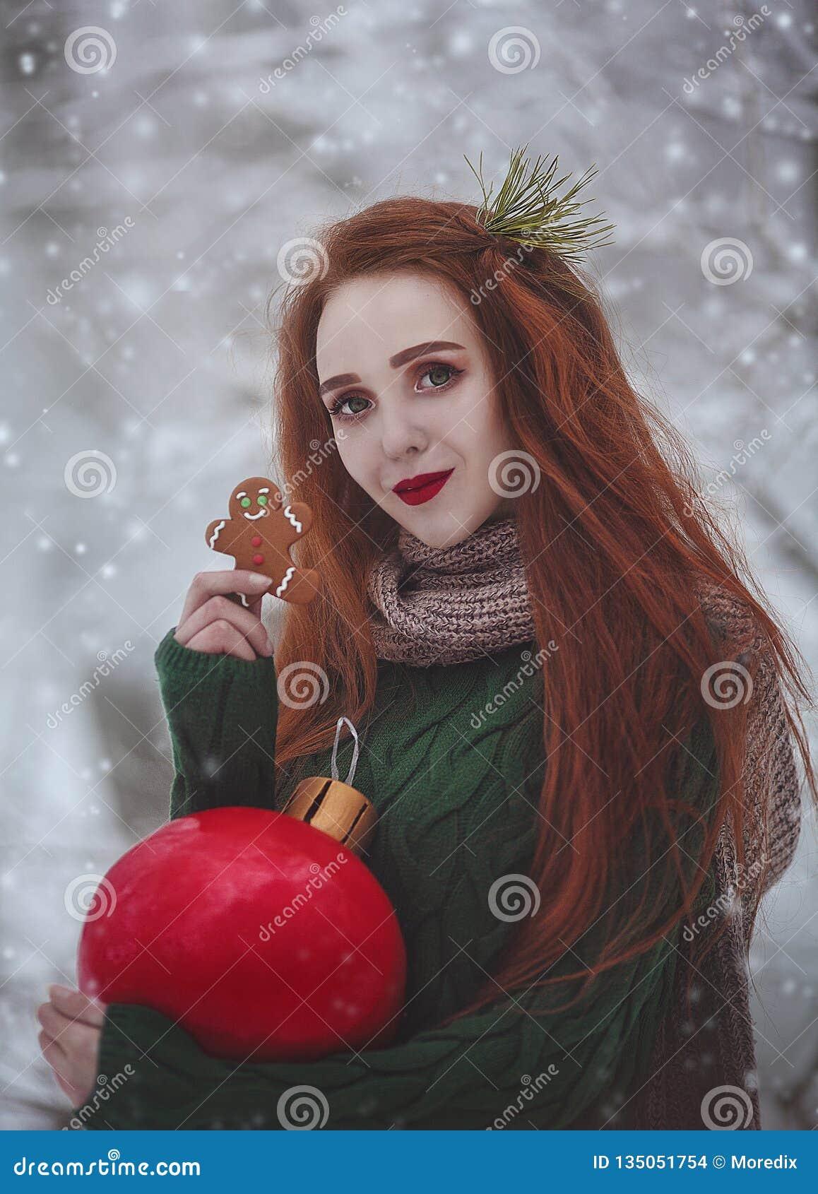 Roodharig langharig glimlachend meisje met een reusachtige Kerstmis rode bal die gemberkoekjes eten Een jonge vrouw met rood binn