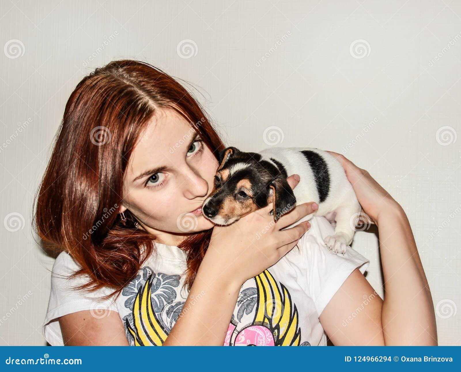 Roodharig meisje die een puppy Jack Russell houden