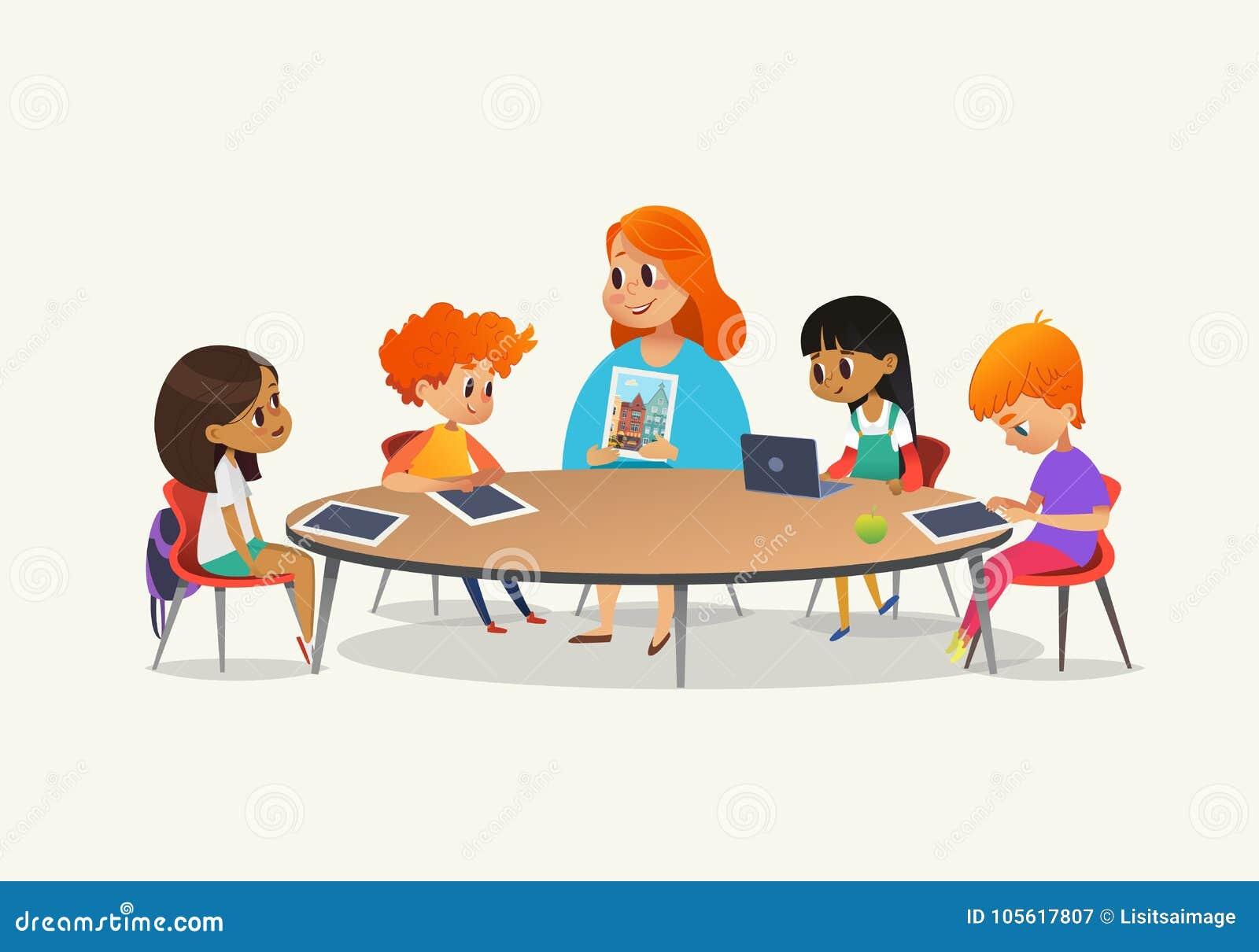Roodharige vrouwelijke leraar die beeld tonen aan kinderen die rondetafel rondhangen bij klasse met laptop en tabletpc Jonge geit