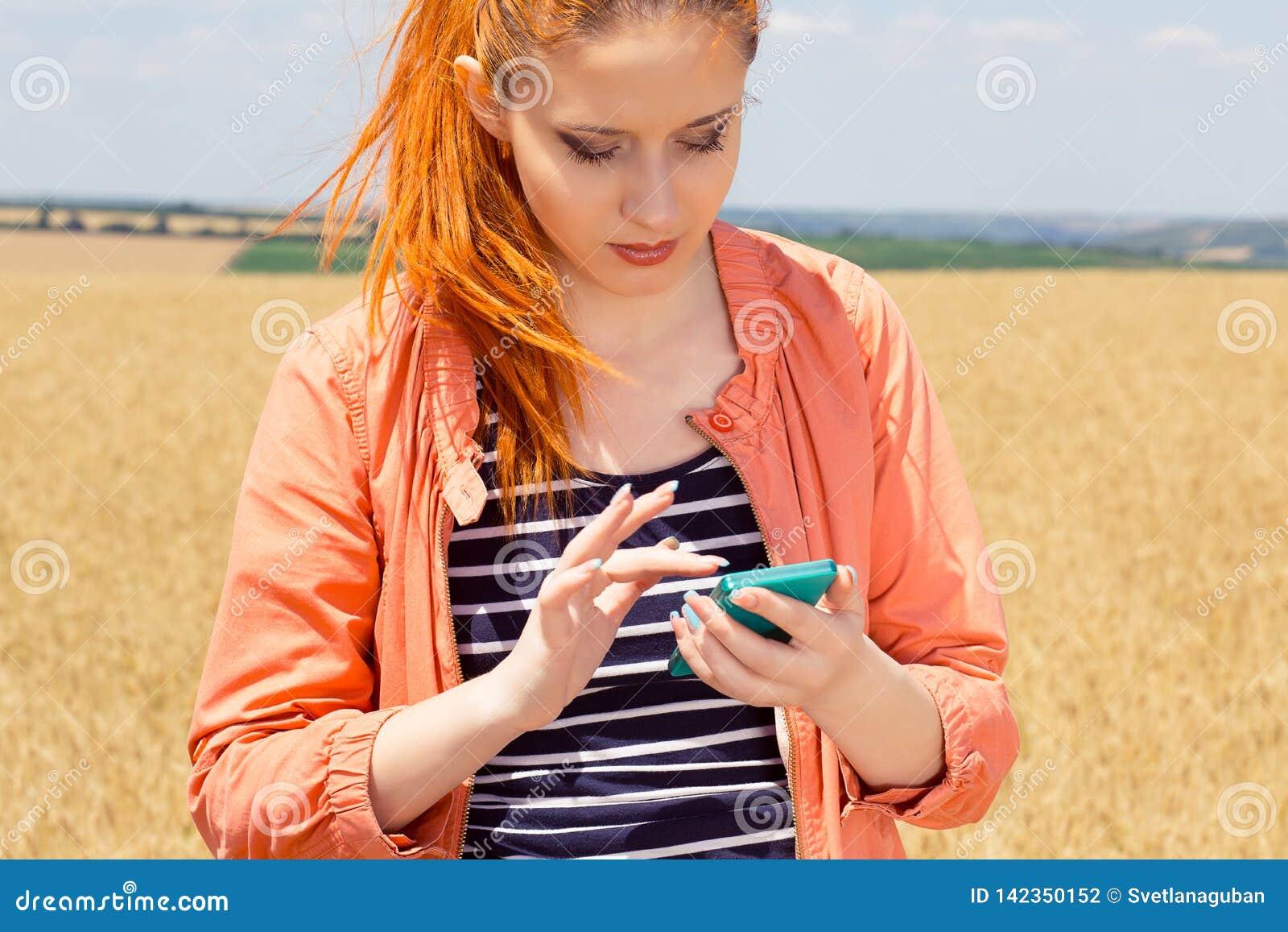 Roodharigevrouw die een bericht verzenden die dekking op mobiele telefoon zoeken