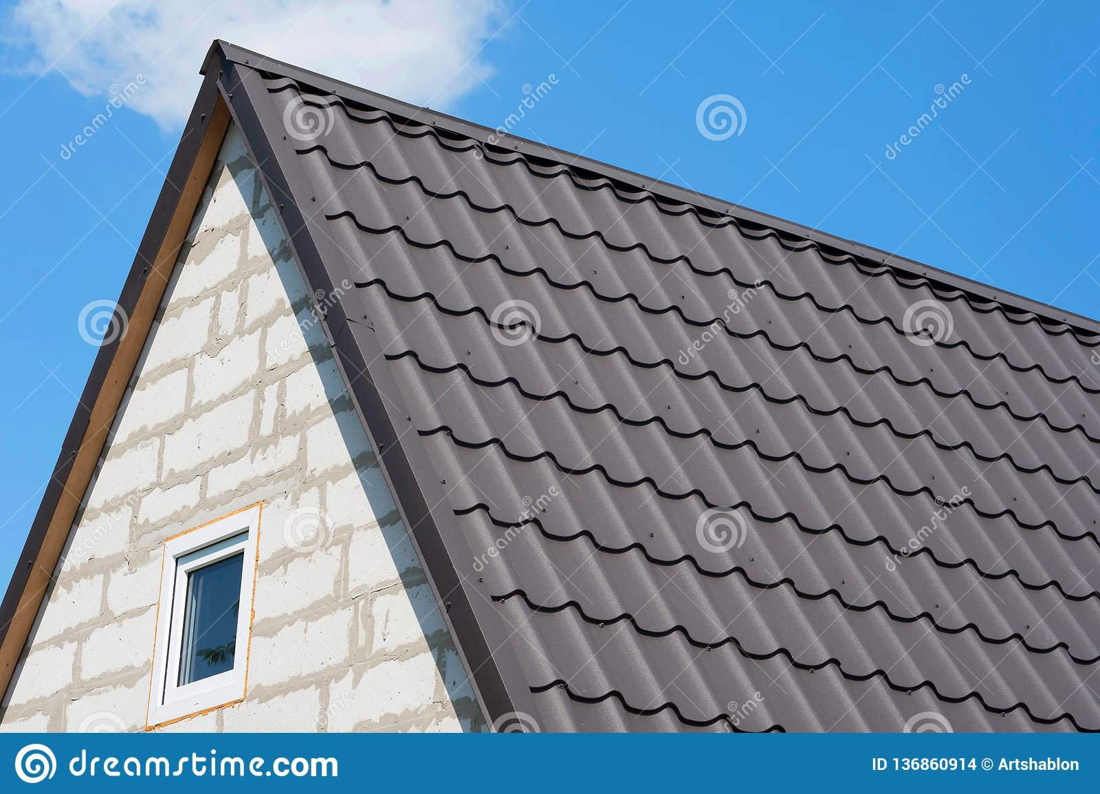 Roof of the house under brown shingles. Corner of the unfinished house close up, against the background of the blue sky