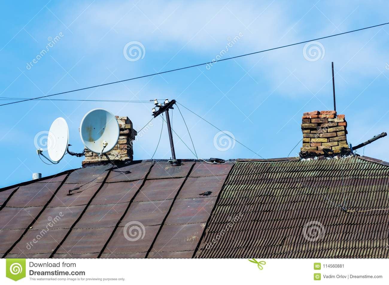 The Roof Of Old House With Chimneys And Television Satellite Wiring Which Is Hot Dishes