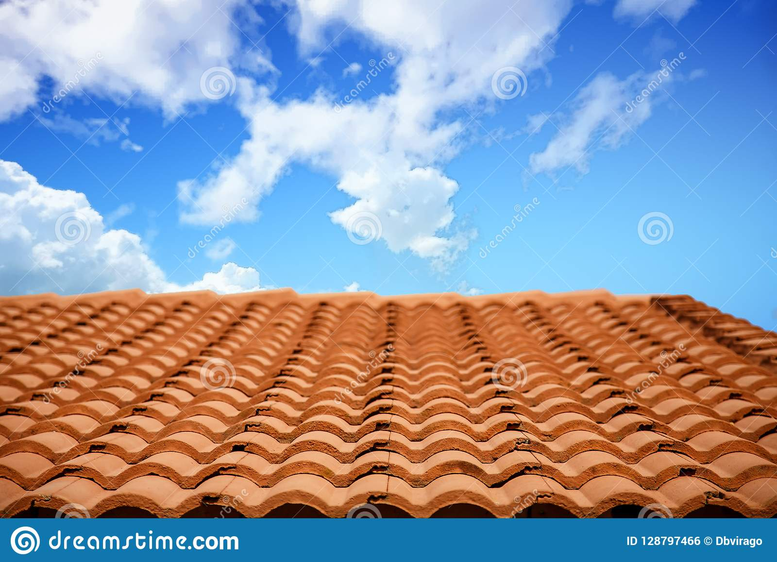 Roof Of Red Clay Tiles Under Cloudy Skies Stock Photo