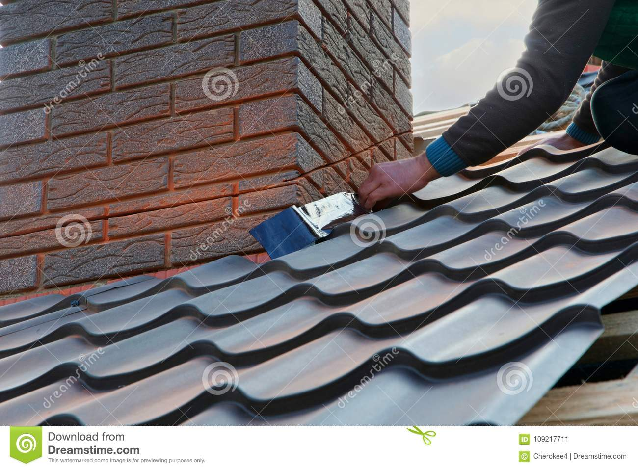 Roofer builder worker attach metal sheet to the chimney. Unfinished roof construction