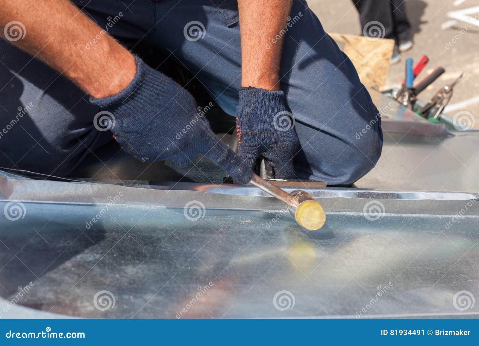 Roofer builder worker finishing folding a metal sheet using rubber mallet.