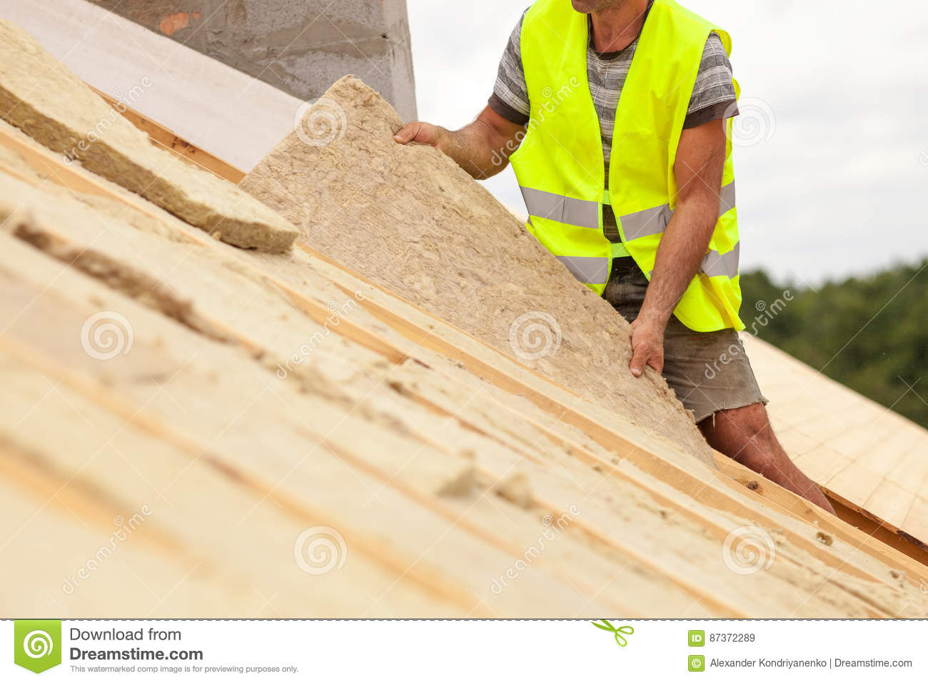 Roofer builder worker installing roof insulation material on new house under construction.