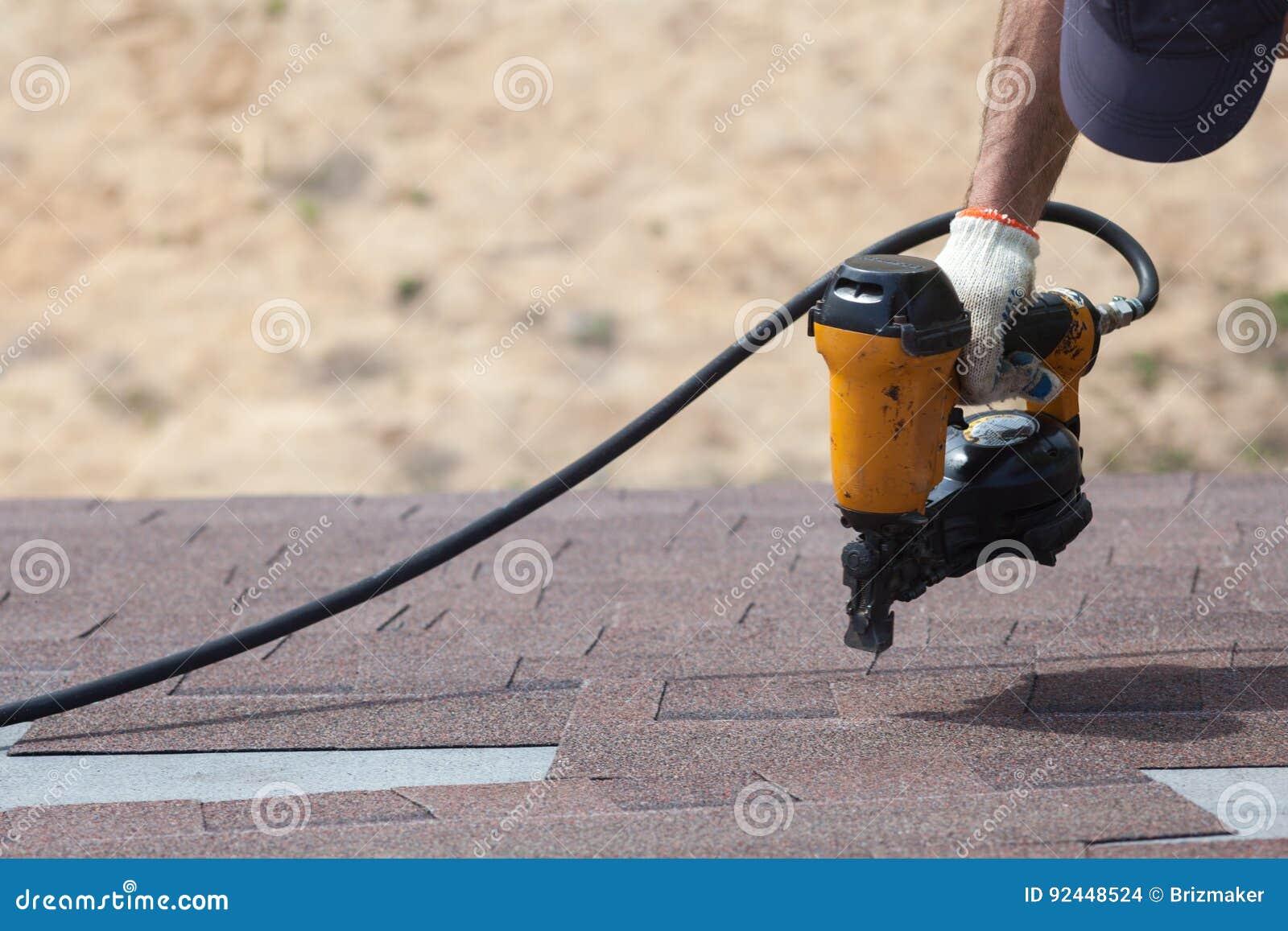 Roofer builder worker with nailgun installing Asphalt Shingles or Bitumen Tiles on a new house under construction.
