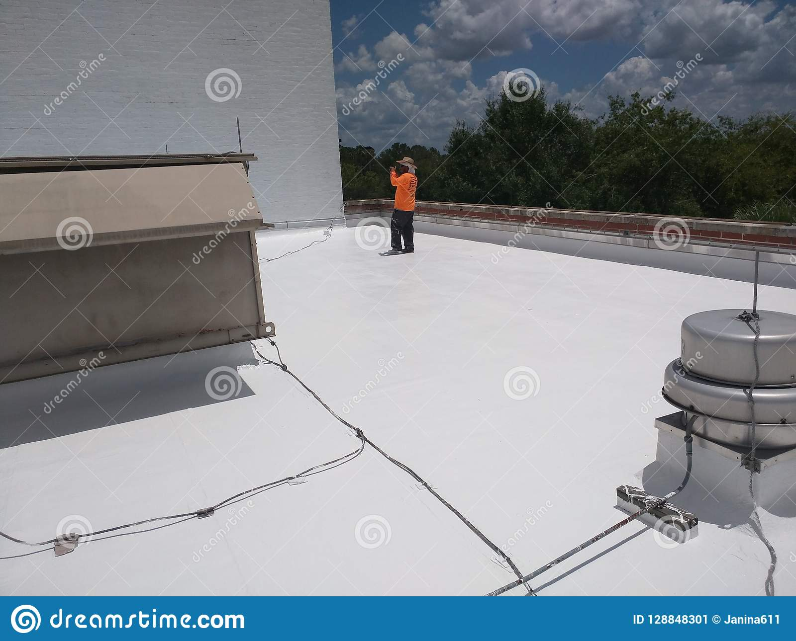 Roofer inspecting a commercial flat roof, EPDM Roofing