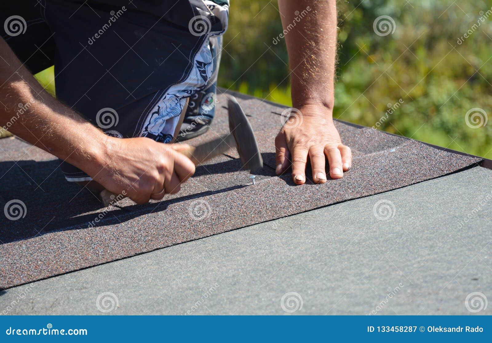 Roofer installant des bardeaux d asphalte sur le coin de toit de construction de maison avec le marteau et les clous Construction