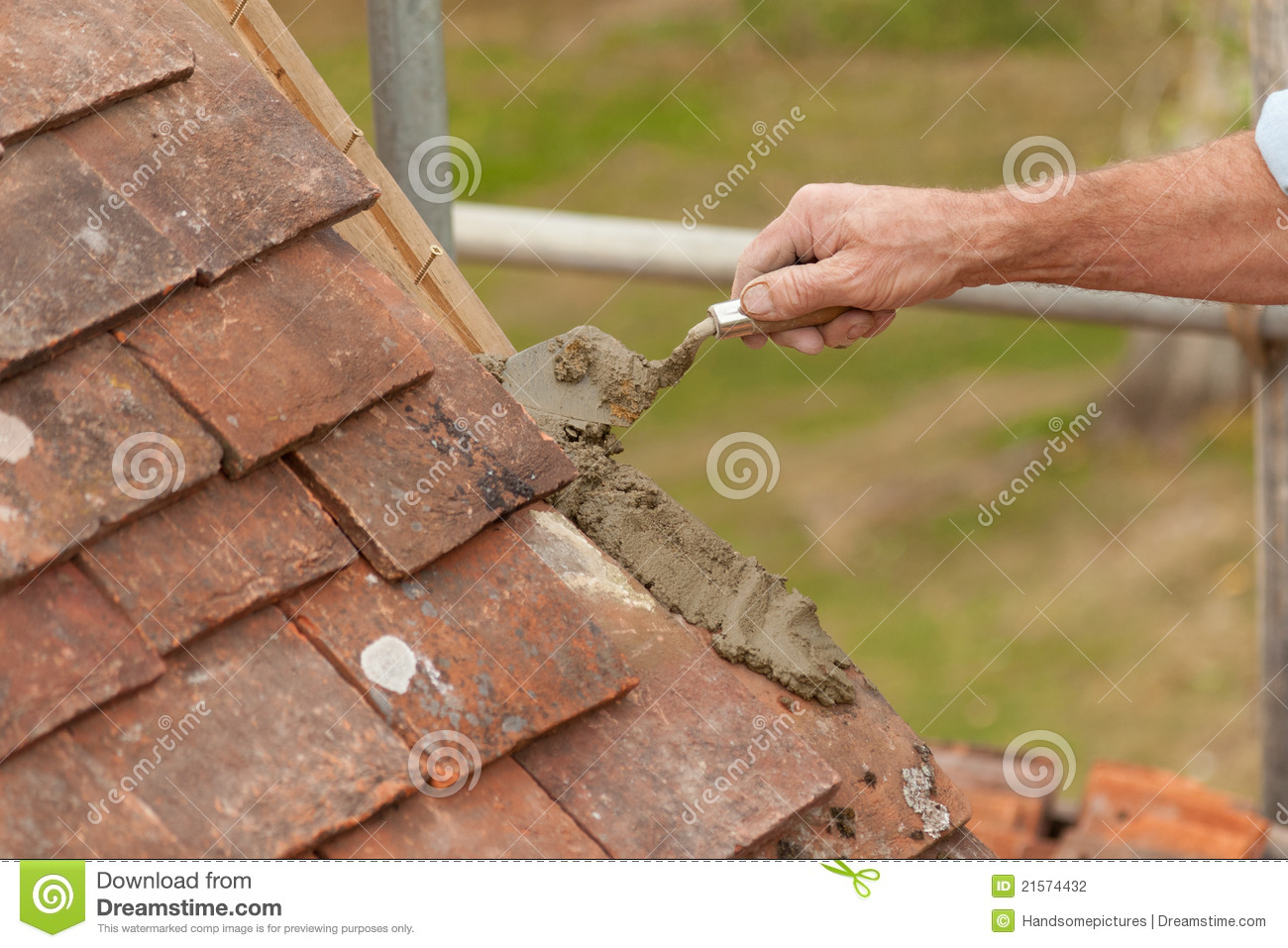Roofer Laying Cement For Edge Tile On Roof Eaves Stock Photo