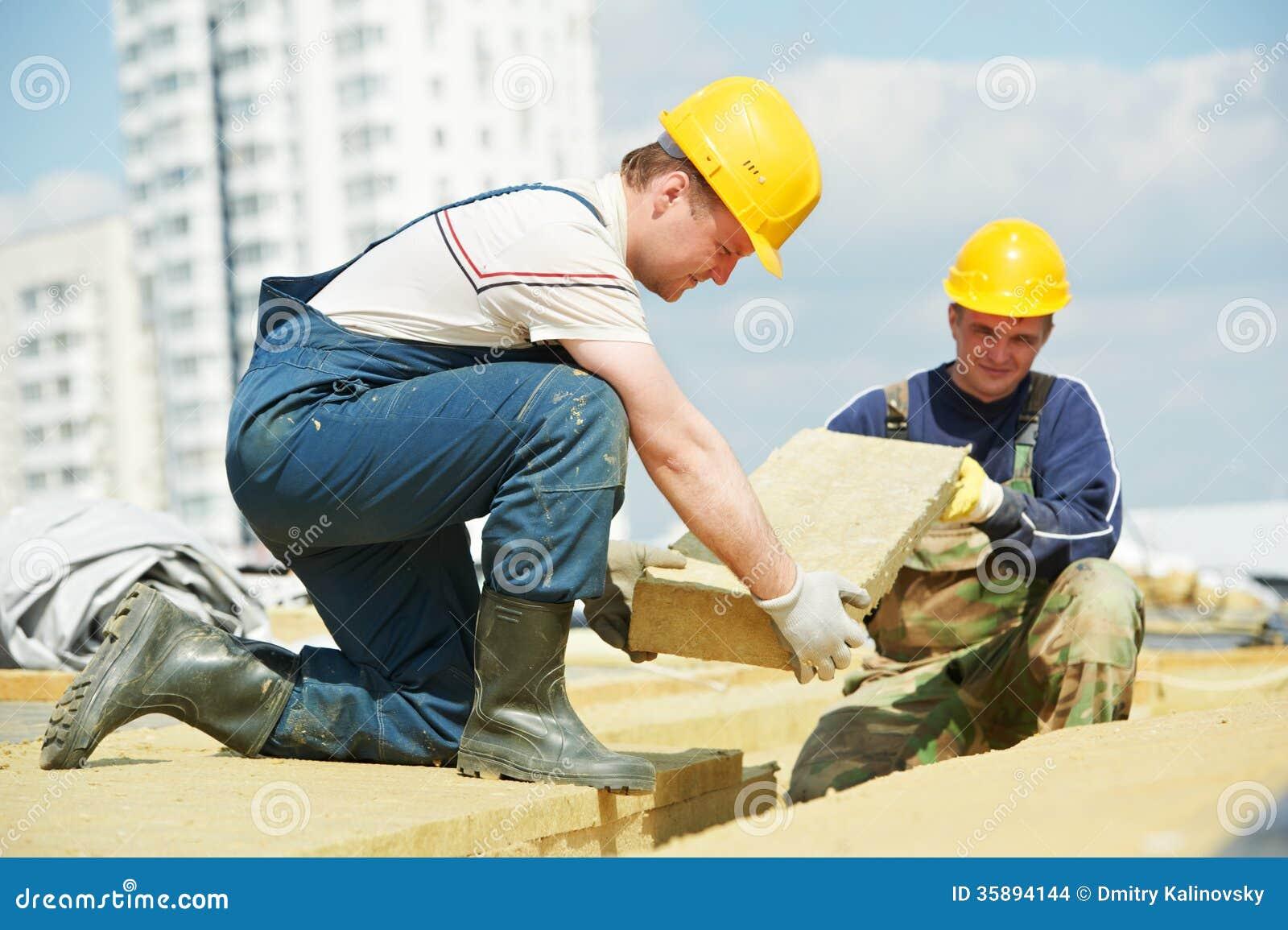 Rooferarbeider die het materiaal van de dakisolatie installeren