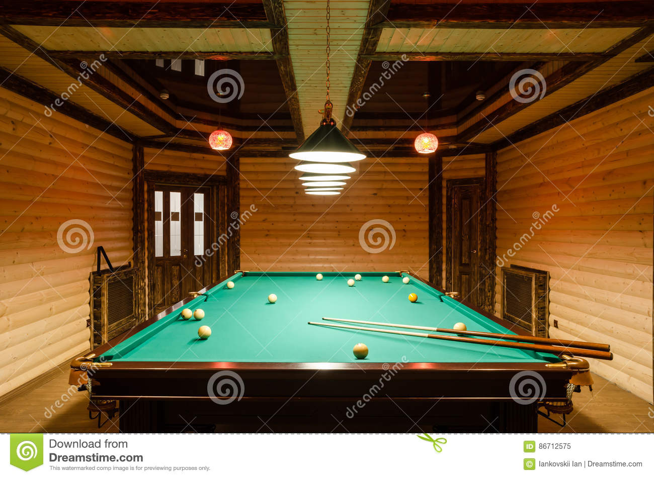 Room billiards decorated in dark wood with low lamps, billiard table with green cloth