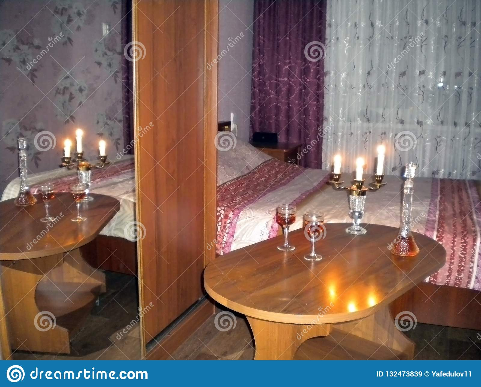 Room with dim light table with candles and brandy