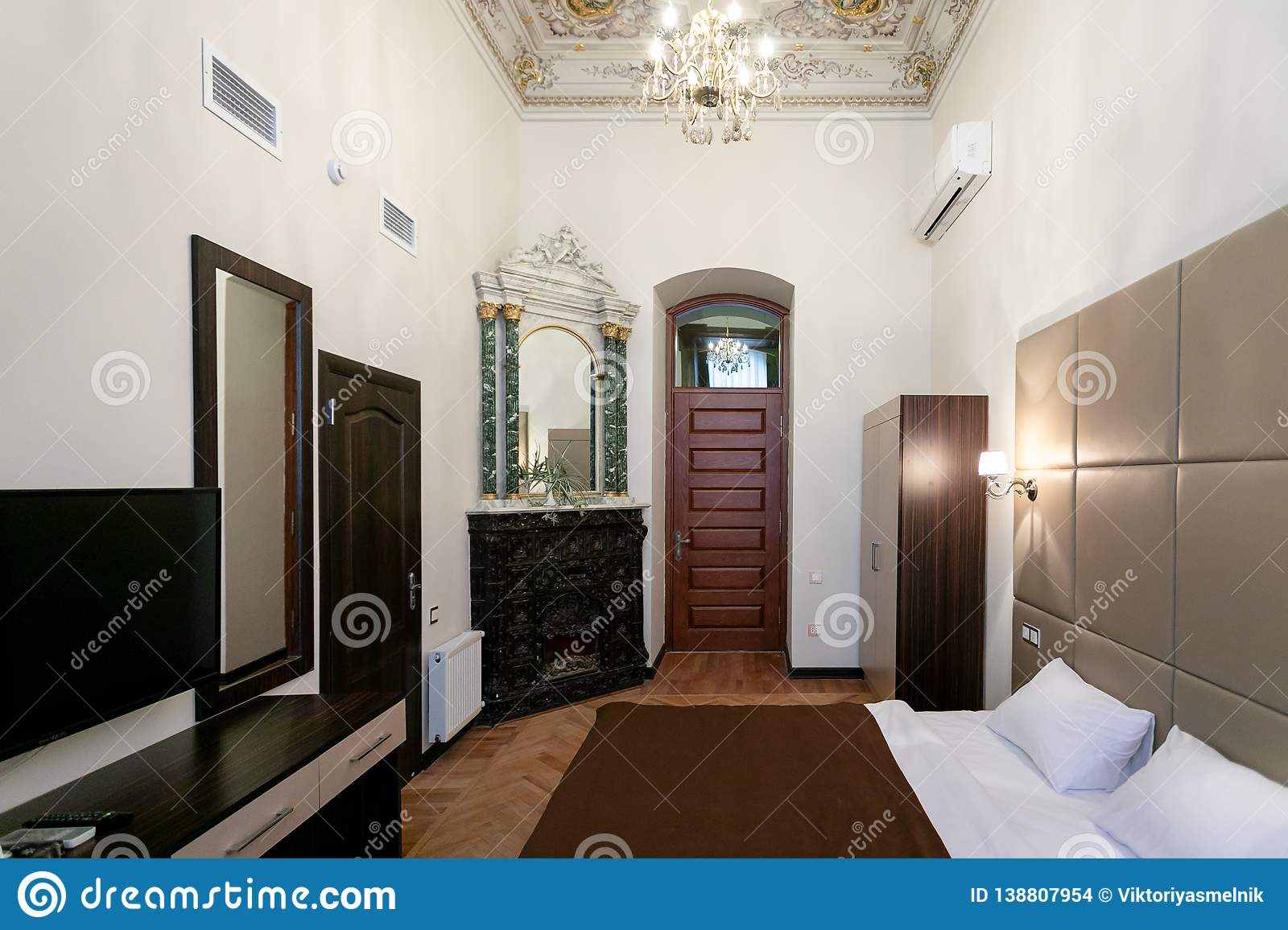 Room with a double bed, TV, mirror on the wall, vintage fireplace, laminate floor, access to the bathroom and hallway, with hand-p