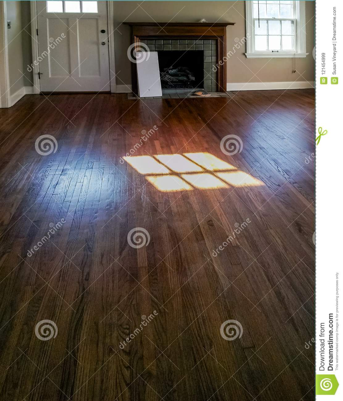Room in empty house with no furniture and wood floors and a fireplace being gotten ready to rent...with reflection of window in th