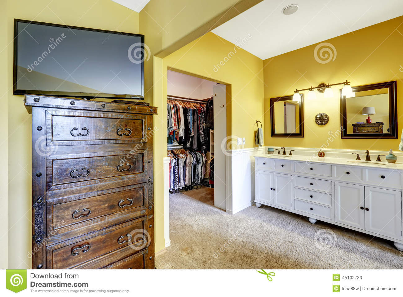 Bright Yellow Room With White Vanity Cabinet, Wooden Dresser With Tv And  Walk In Closet