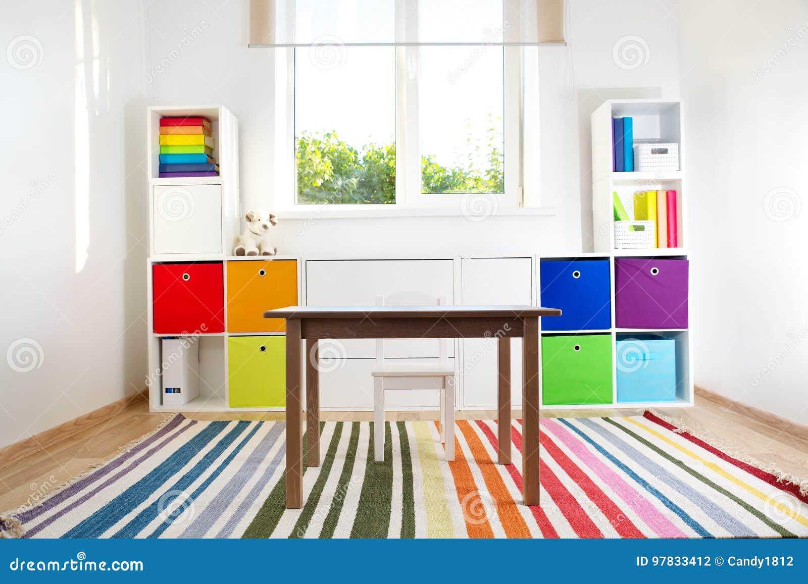 Rooom colorido de los niños con las paredes y los muebles blancos