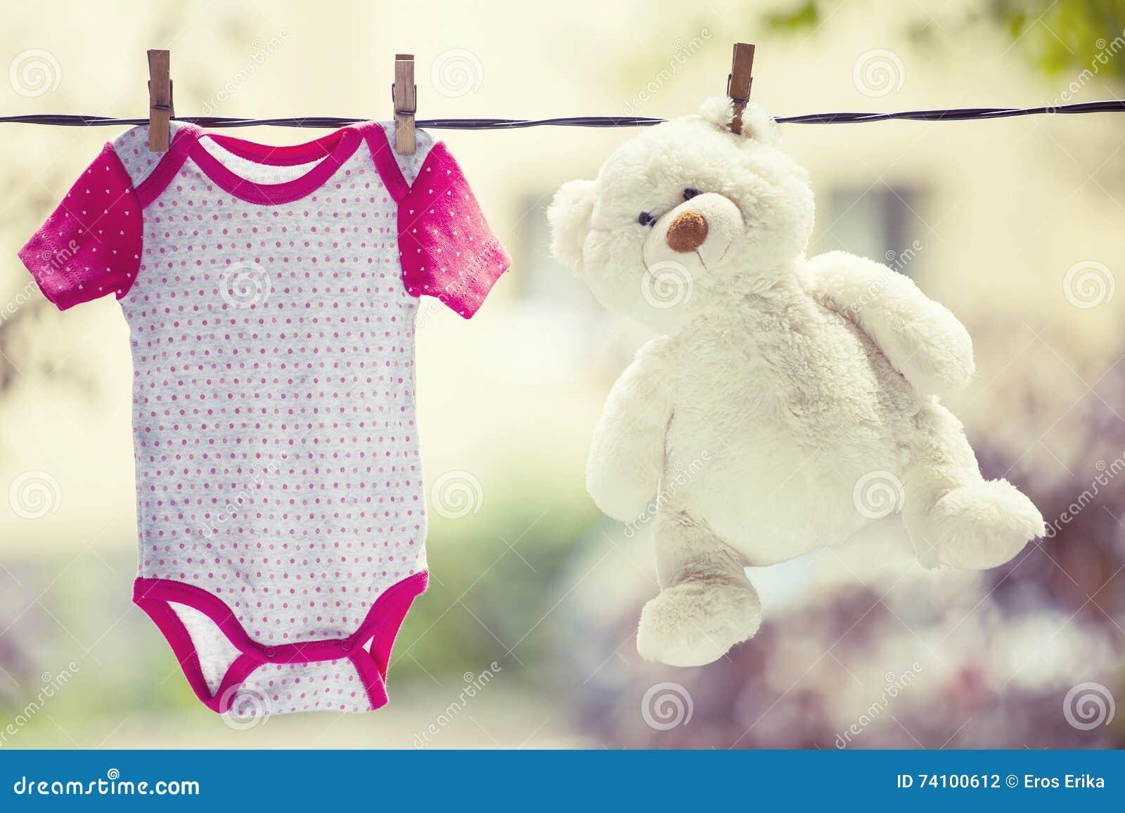 48cace254 Ropa del bebé y ejecución del oso de peluche en la cuerda para tender la  ropa