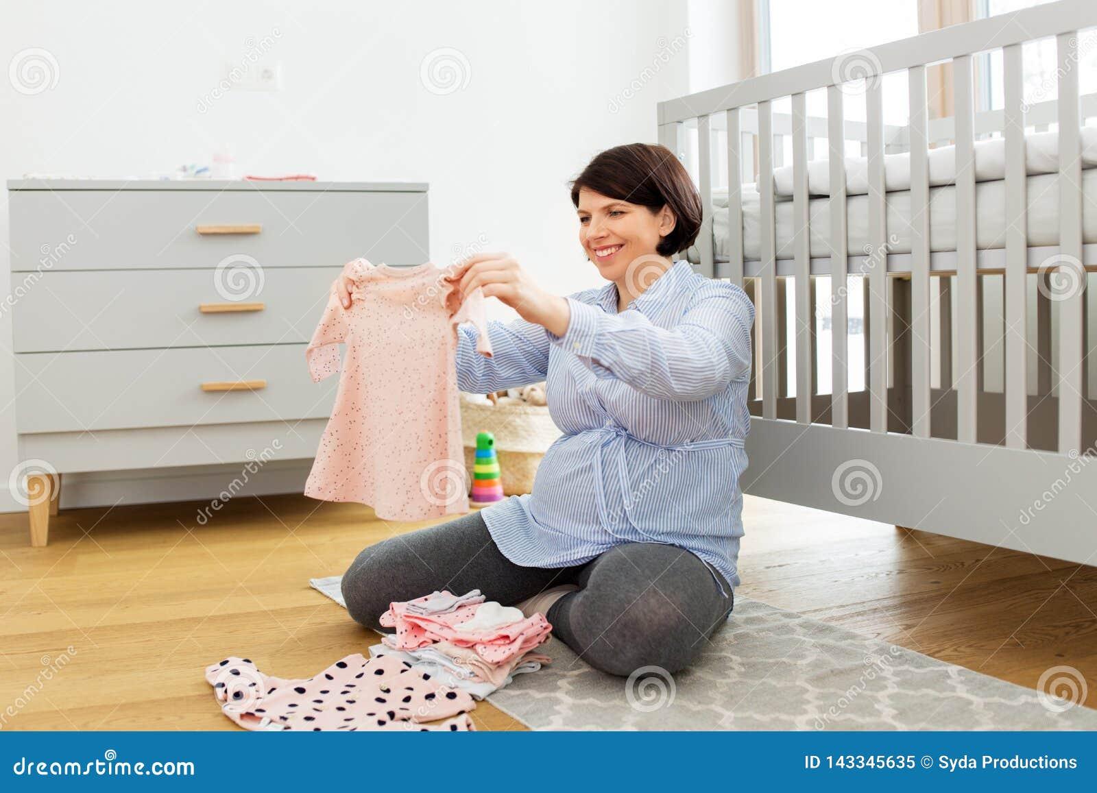 Ropa feliz del bebé del ajuste de la mujer embarazada en casa