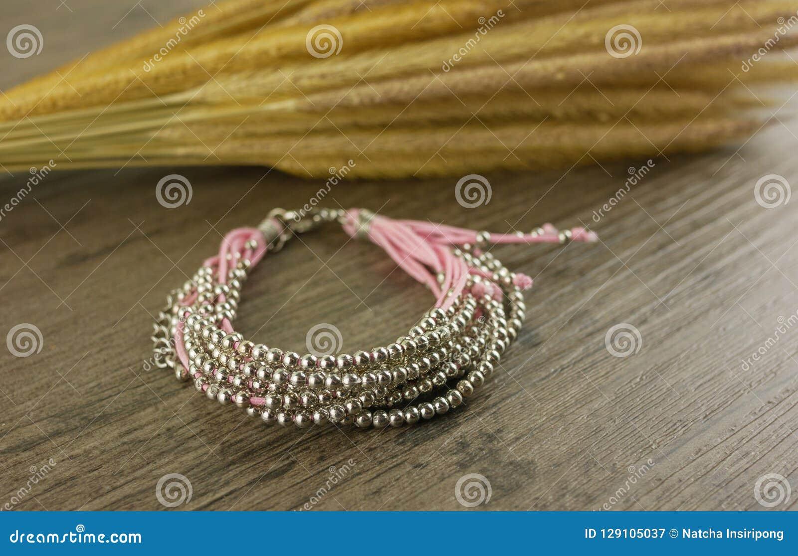 Rosa Armband auf hölzernem Hintergrund