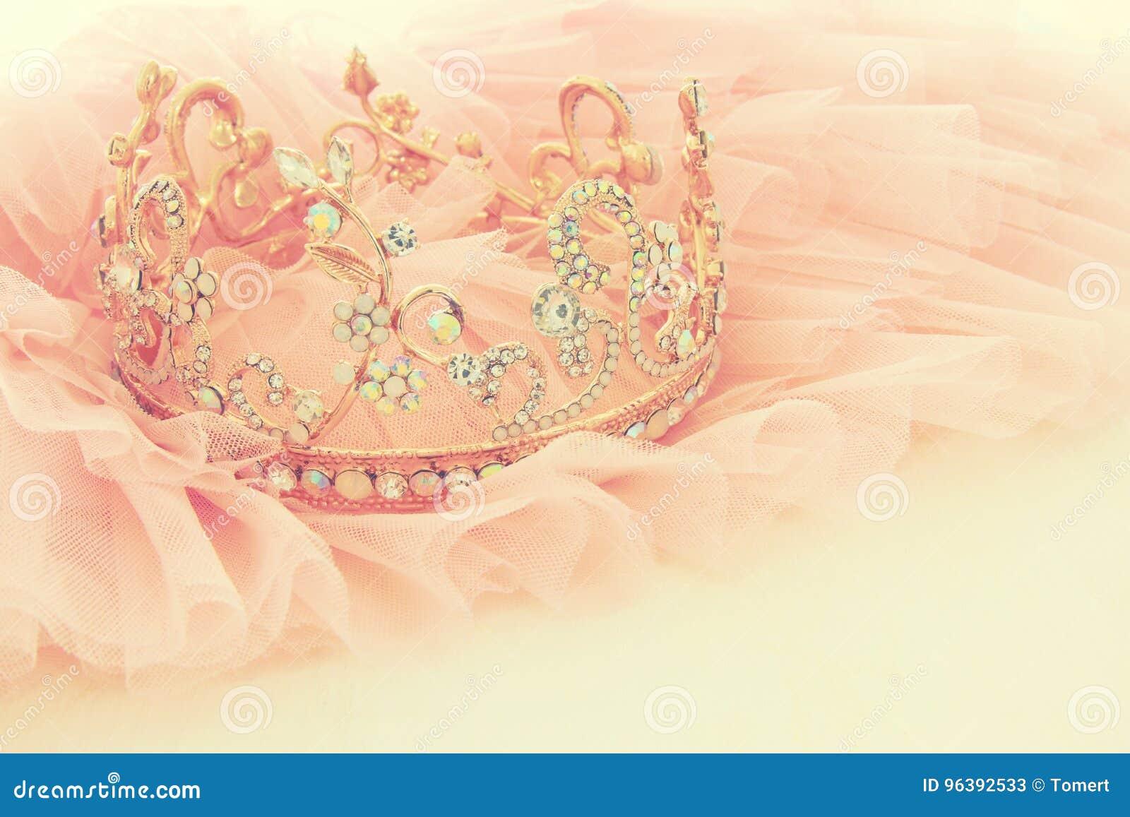 Rosa Chiffon- Kleid Weinlesetulles und Diamanttiara auf hölzerner weißer Tabelle Hochzeit und girl& x27; s-Parteikonzept