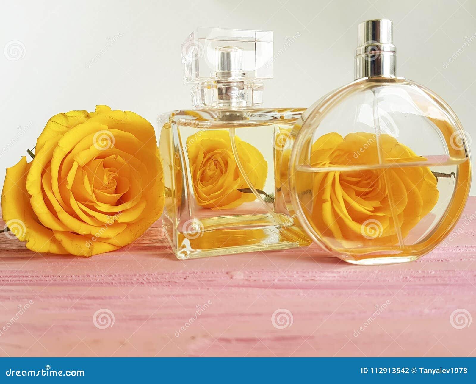 Rosa di giallo della bottiglia di profumo su una decorazione di legno