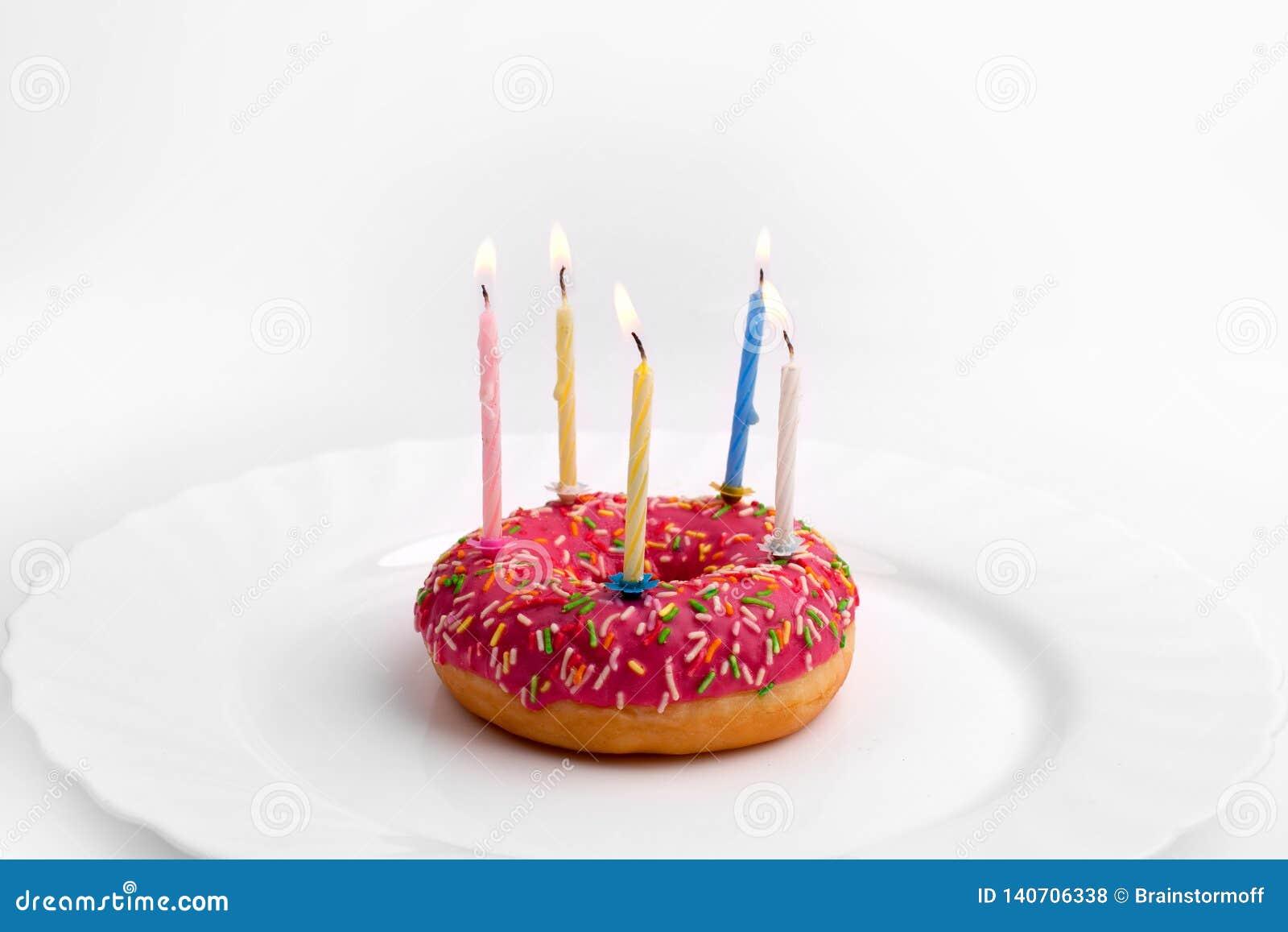 Rosa Donut auf weißer Platte wie Geburtstagskuchen mit Kerzen auf weißem Hintergrund