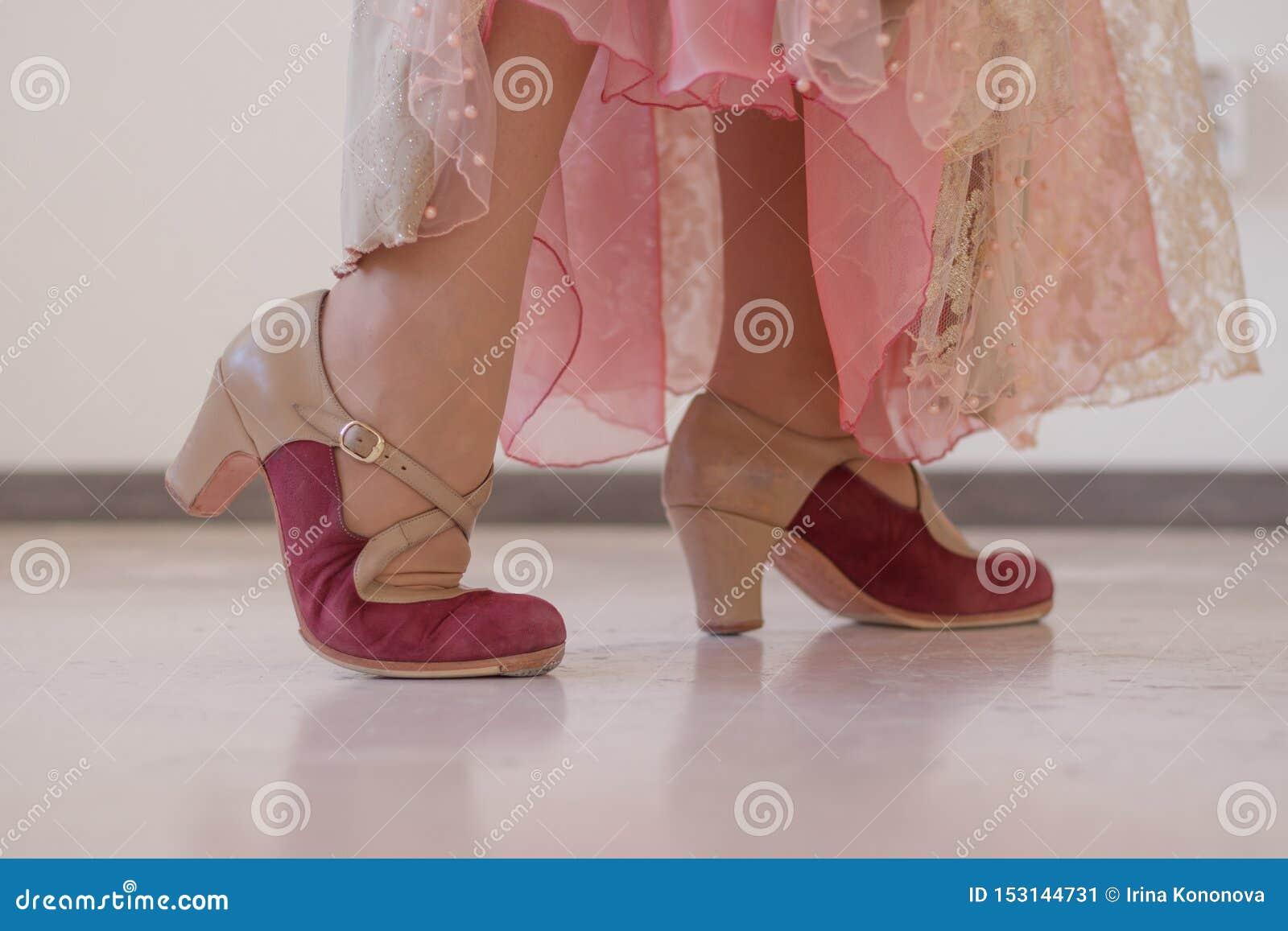 Rosa e sapatas bege para a dança do flamenco nos pés das mulheres