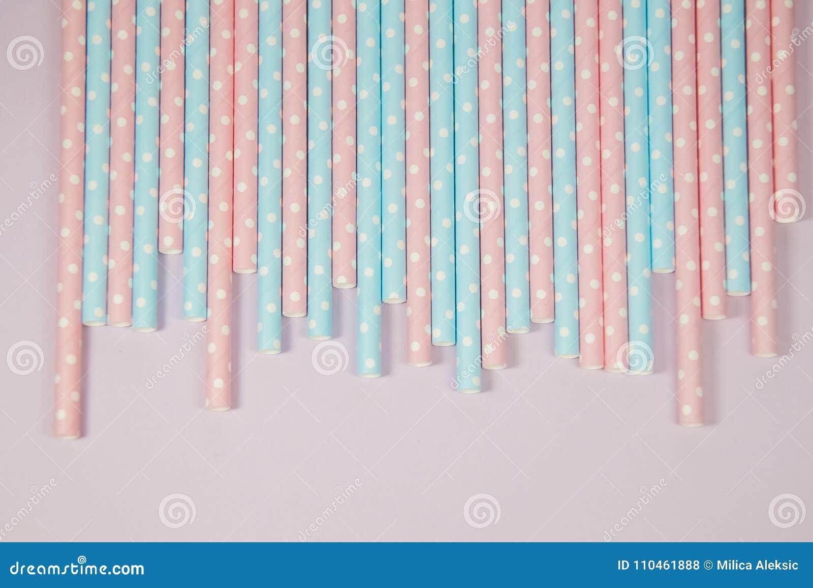 Rosa färg- och blåttpricksugrör på den rosa bakgrunden
