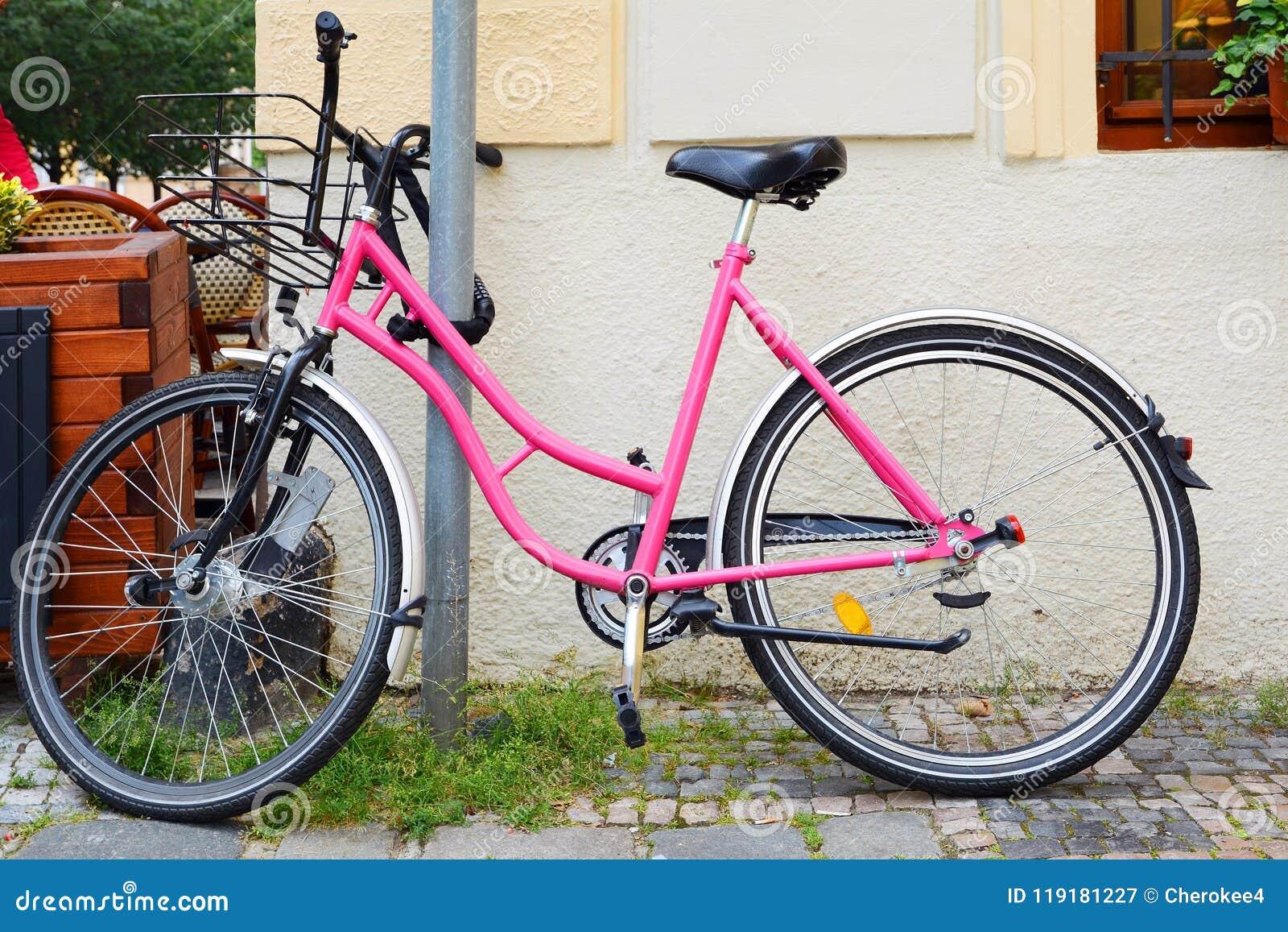 Rosa färger cyklar cyklar som är tillgängliga för hyra, parkerat i centret