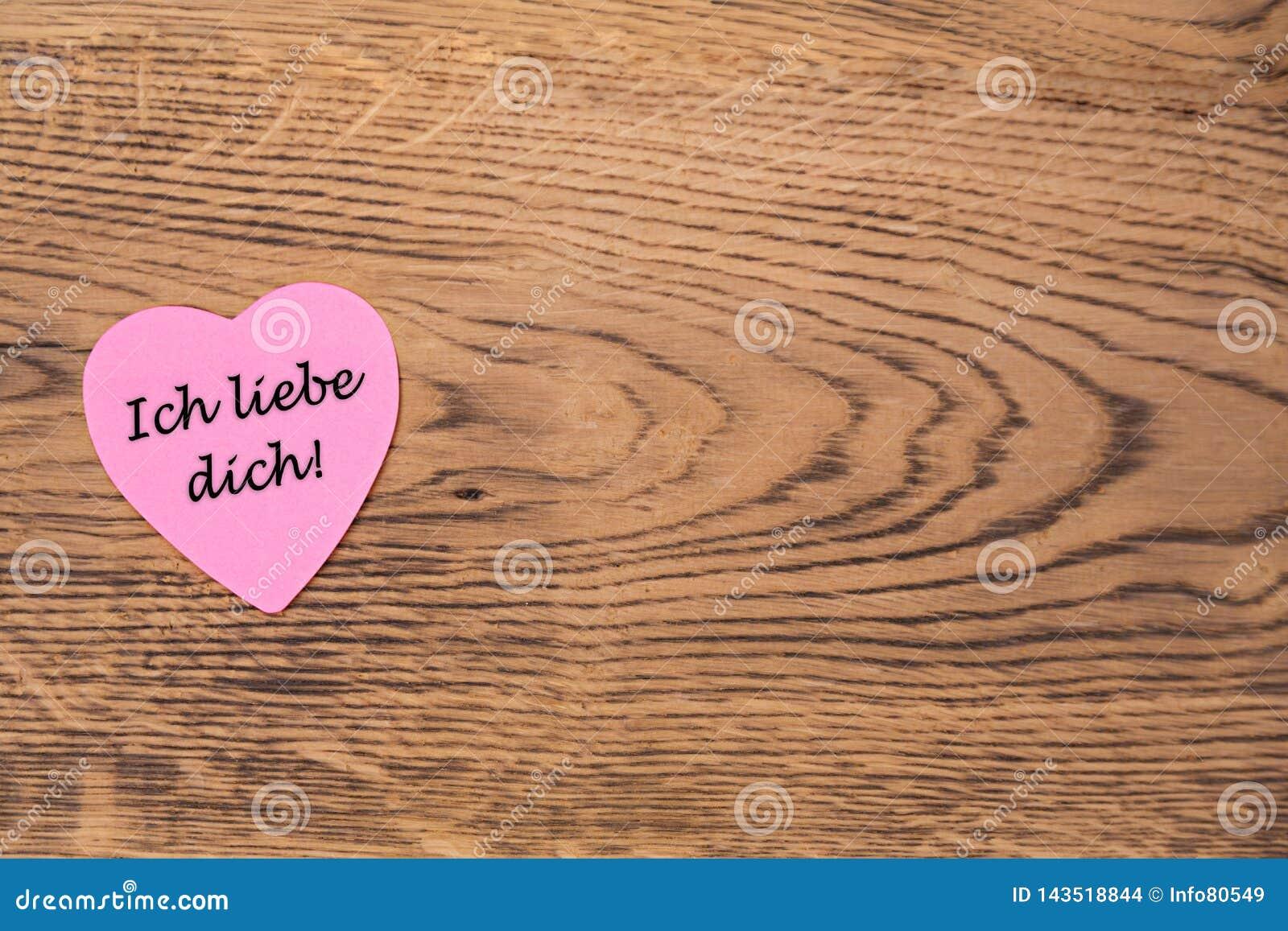 Rosa färghjärta stolpe-honom med texten 'Ich liebedich 'på en träbakgrund ?vers?ttning: ??lskar jag dig ?,