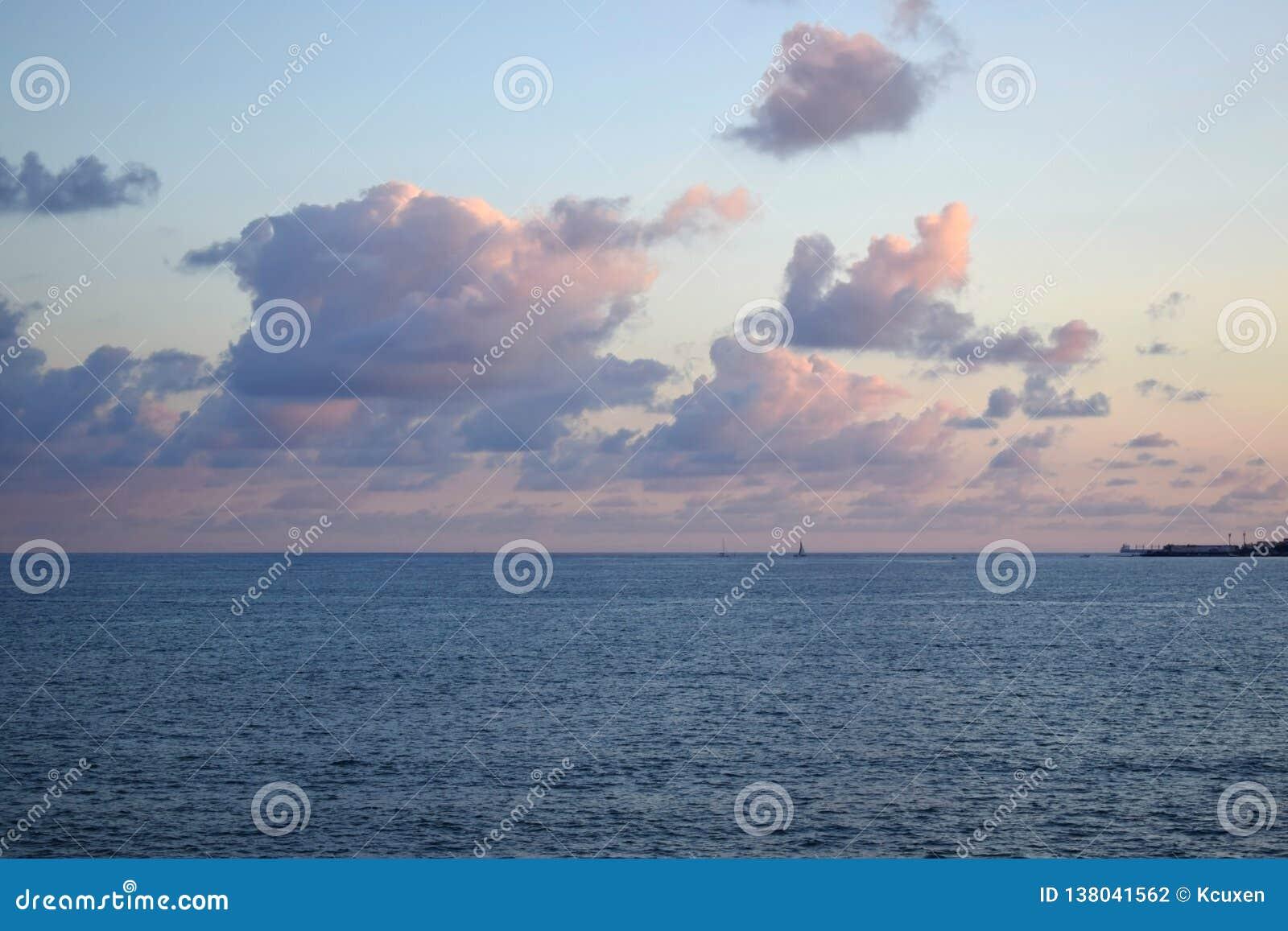 Rosa fluffiga moln över havet