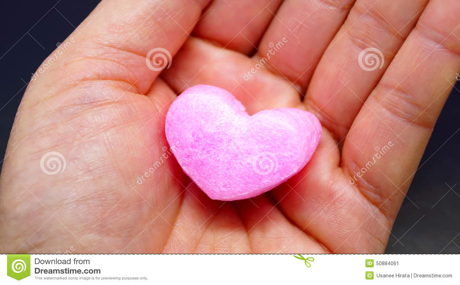 Rosa Herz auf Frauenhand