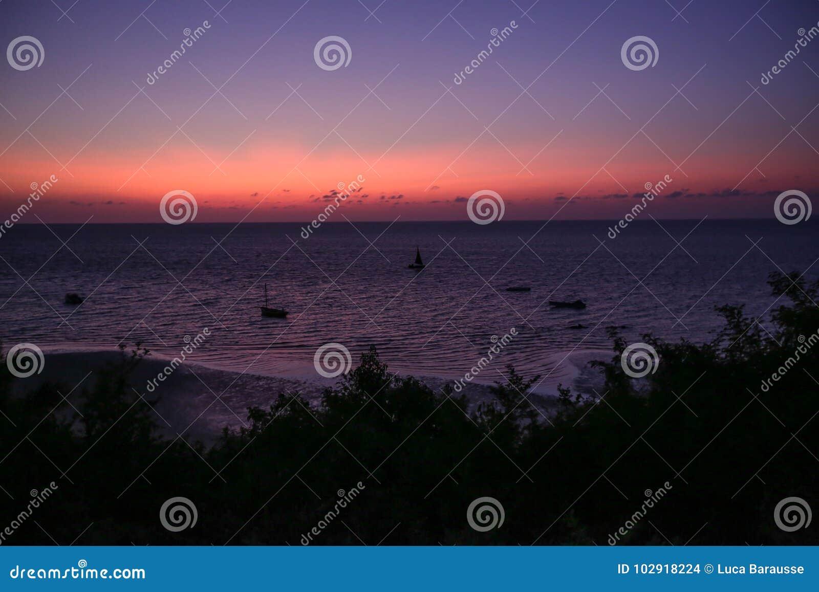 Rosa Himmel über dem Ozean mit Segelbooten