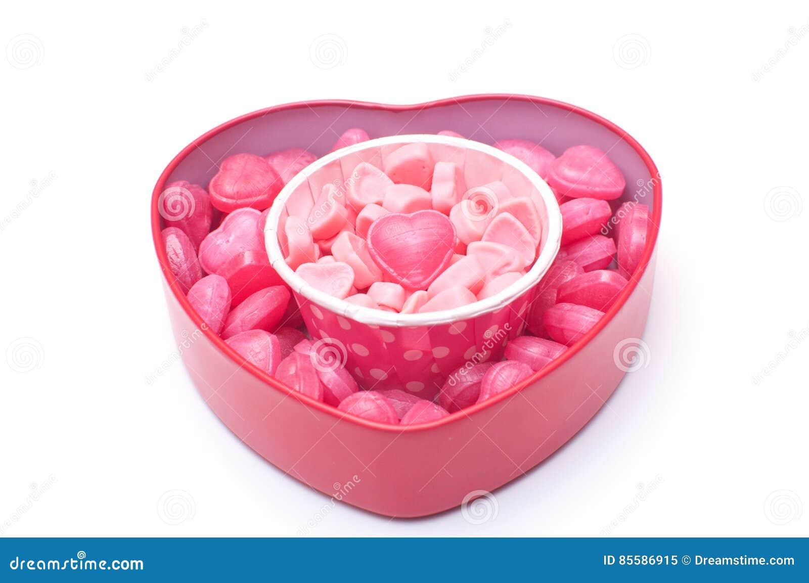 Rosa hjärtagodisar i kopp och i hjärtaform boxas för valentin D
