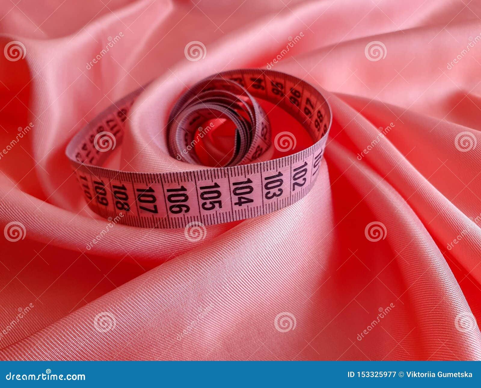 Rosa måttband med svarta nummer på en vit naturlig eller tygbakgrund Nära övre sikt av det mäta bandet Teman: banta
