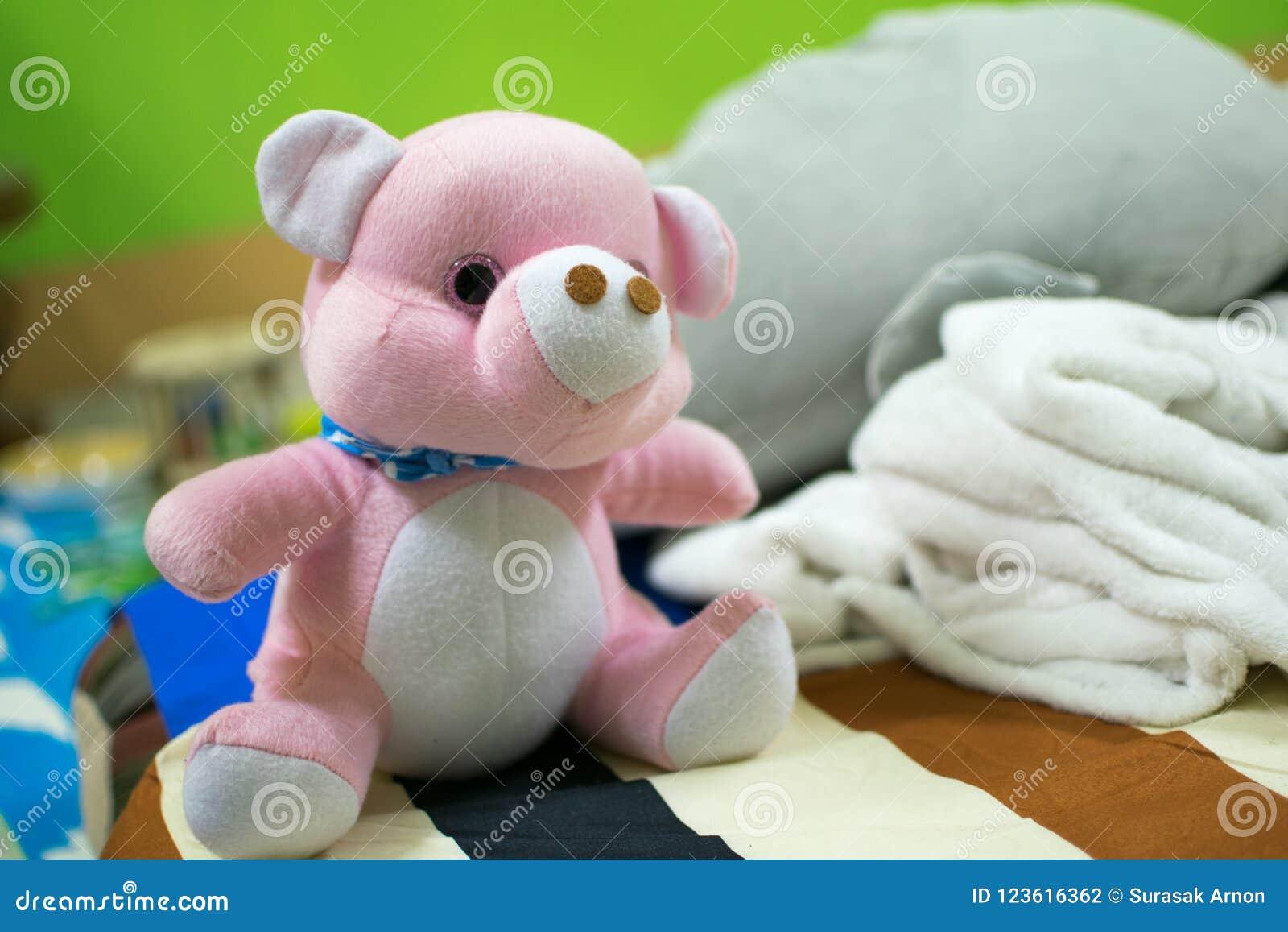 Rosa nallebjörn som förläggas på sängen