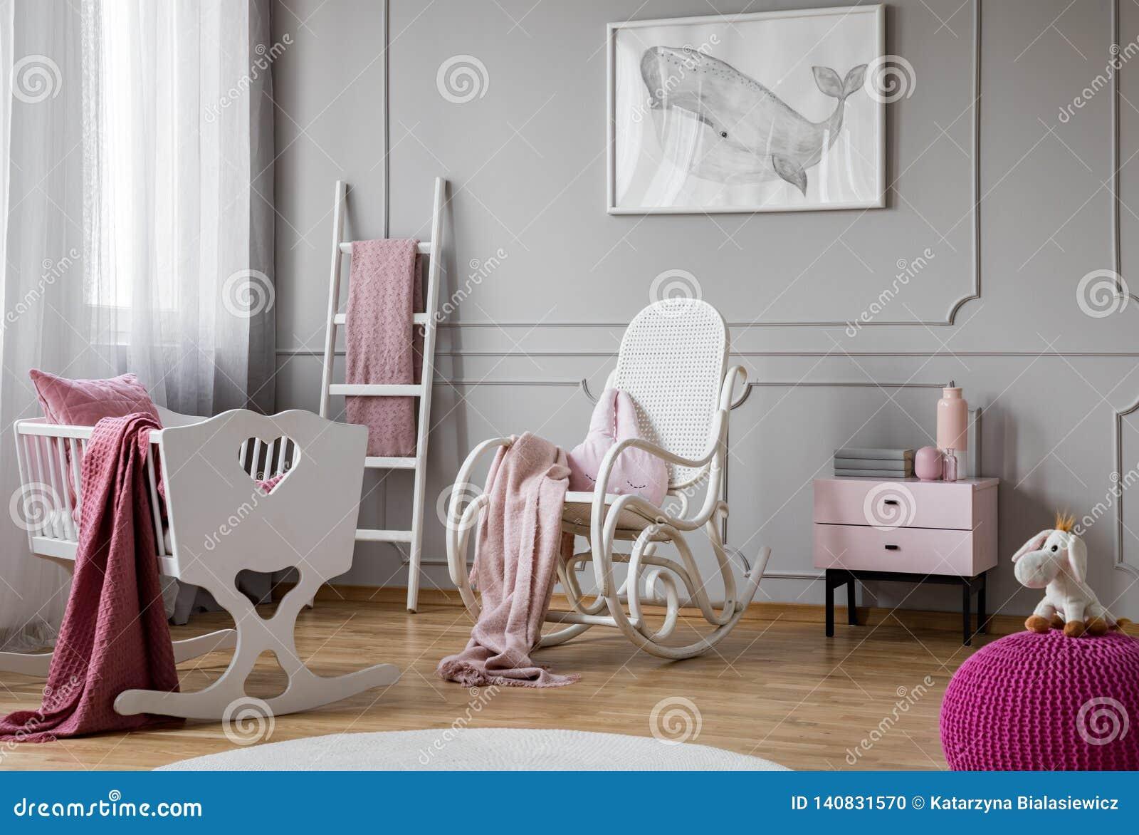 Rosa Pastelldecke auf weißem Schaukelstuhl im geräumigen Babyrauminnenraum mit Wiege, skandinavischer Leiter und nightstand