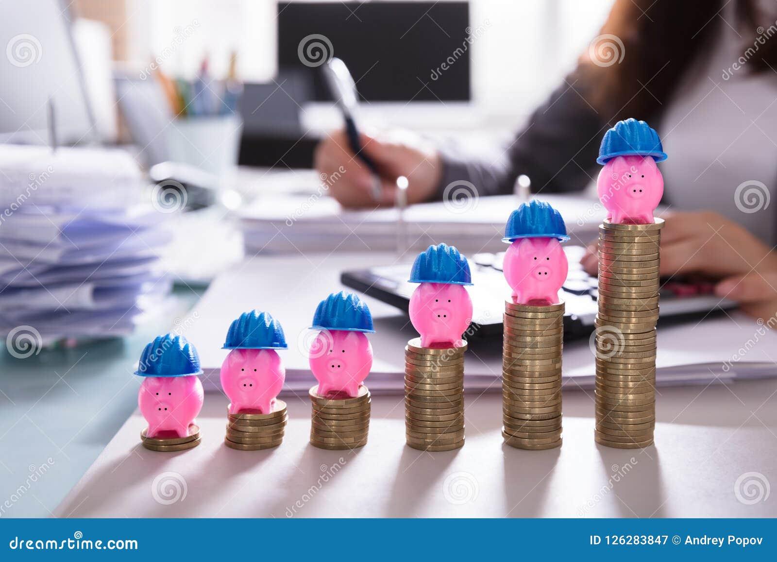 Rosa Piggybank med den hårda hatten över att öka staplade mynt