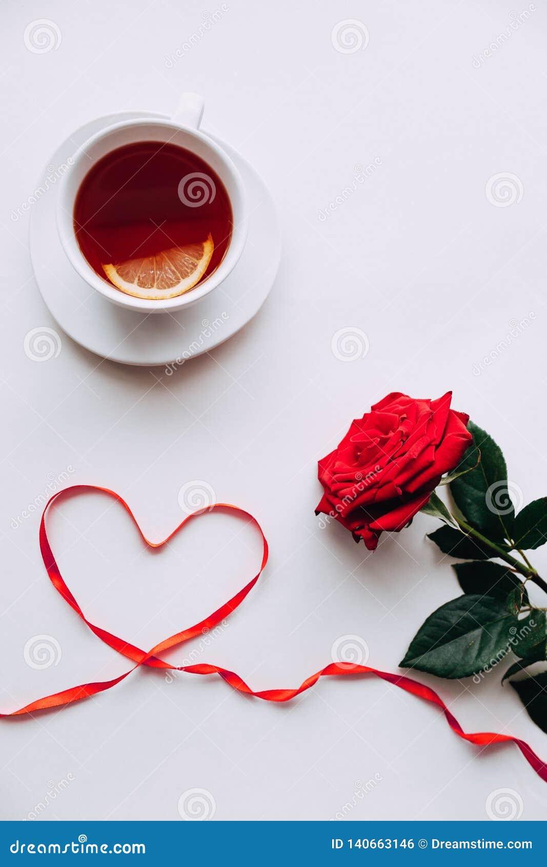 Rosa roja en un fondo blanco, cinta en el corazón del ide el 8 de marzo