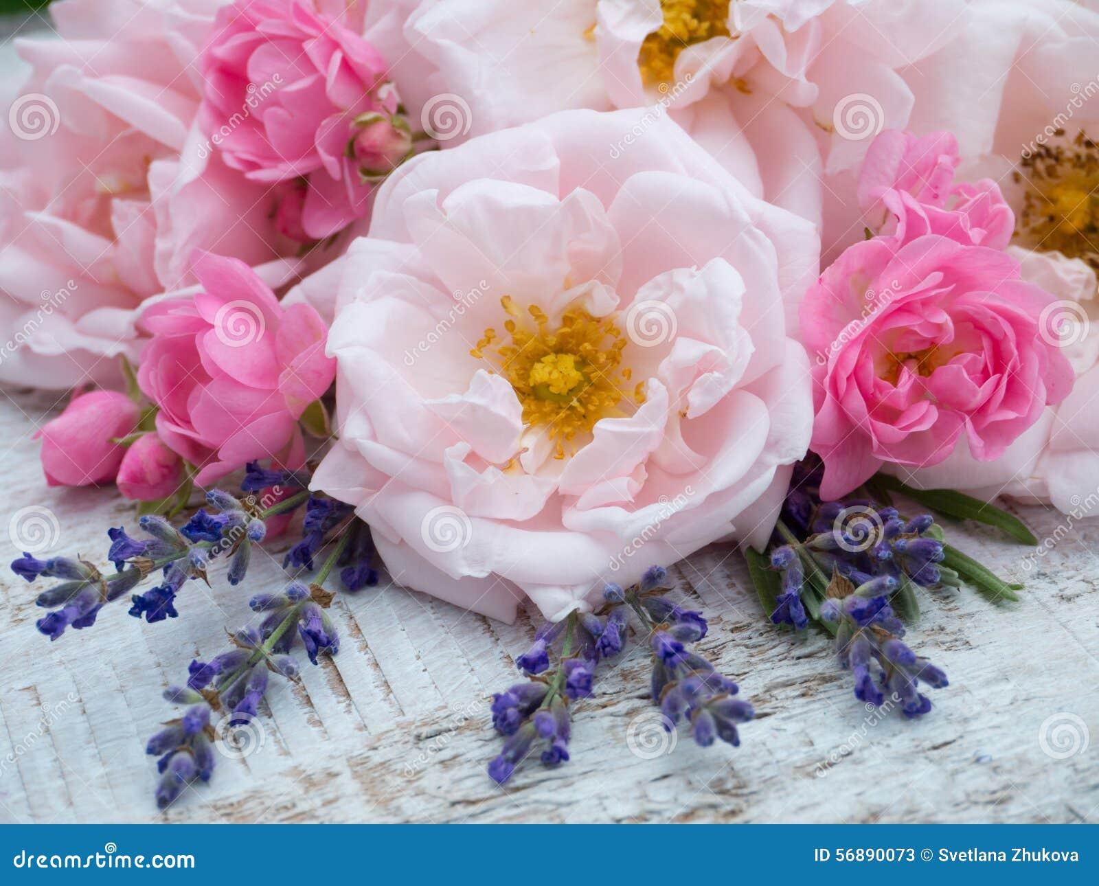 Rosa Rosen und Lavendelblumenstrauß auf dem rustikalen Hintergrund