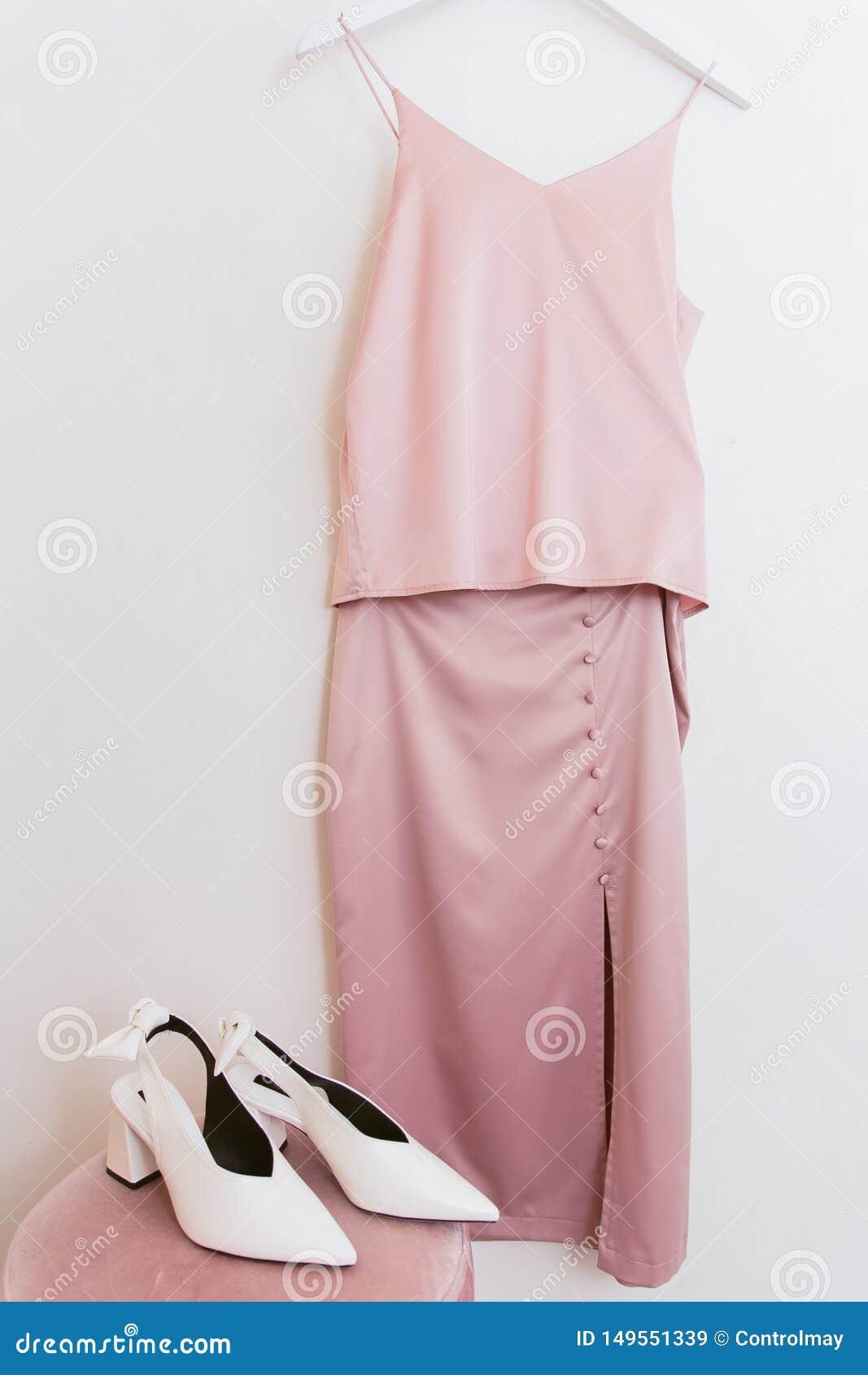 Rosa Seidenbluse und Rock auf einem Aufhänger in der Umkleidekabine und weißen Schuhen auf dem Puff Kleidung und Kleidung im Umkl