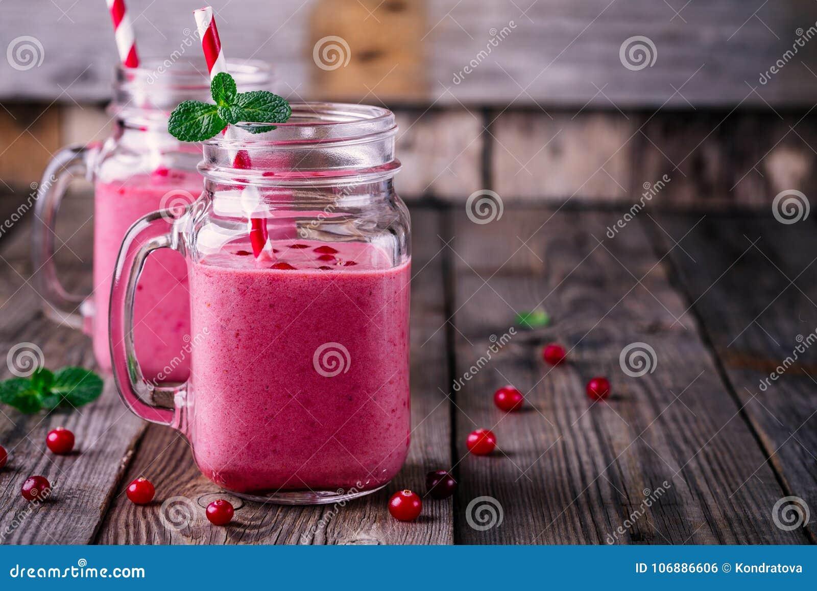 Rosa smoothie med lösa tranbär i murarekrus med mintkaramellen och sugrör på träbakgrund