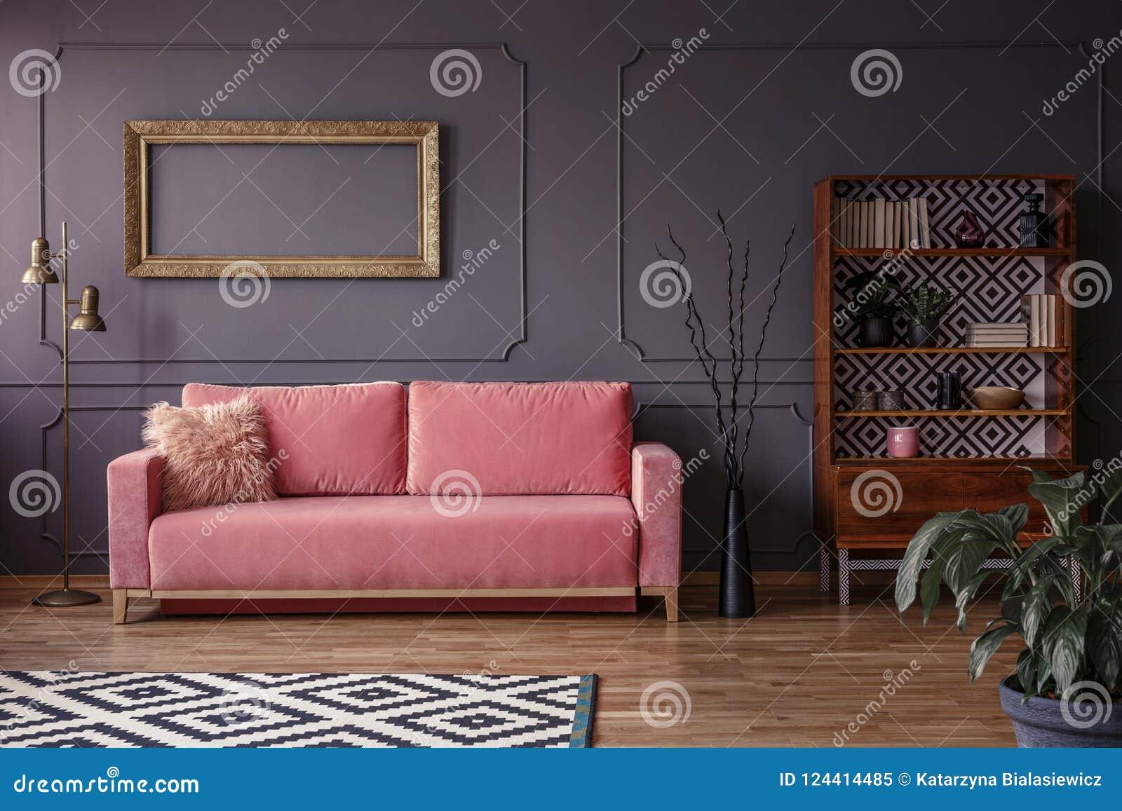 Rosa soffa mot den gråa väggen med modellen av den guld- ramen i elega