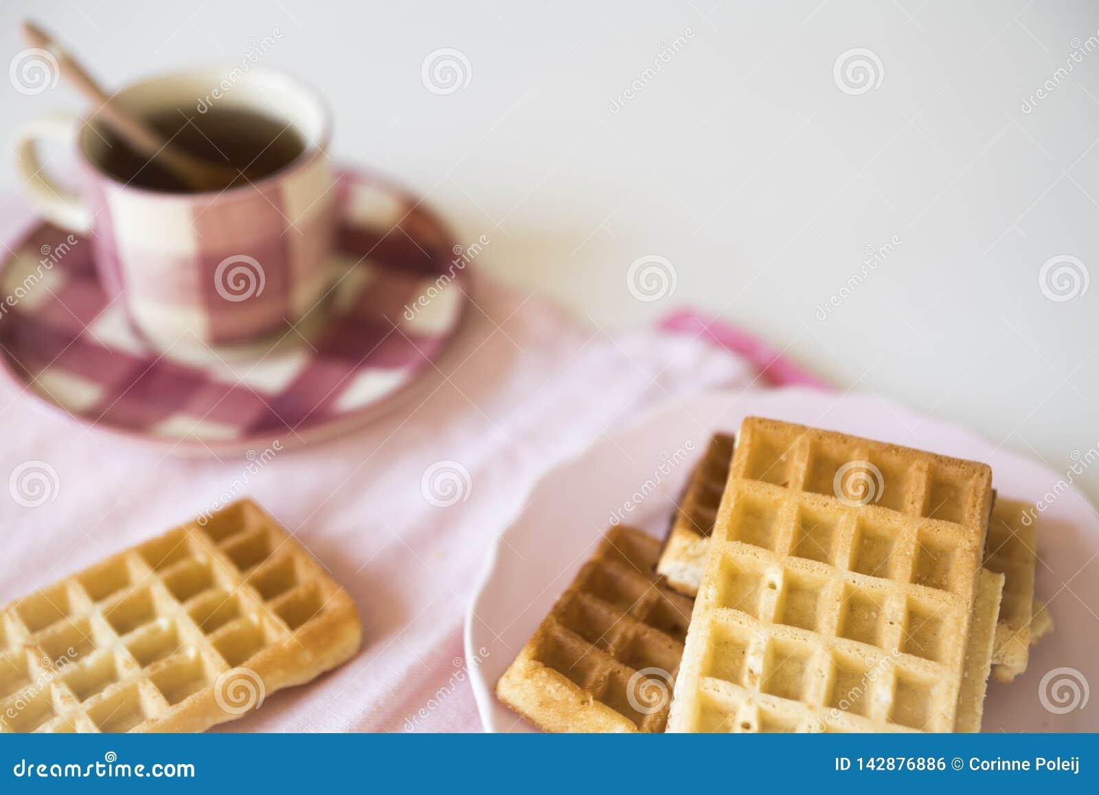 Rosa Tasse Tee und Brüssel-Waffeln auf weißer Tabelle