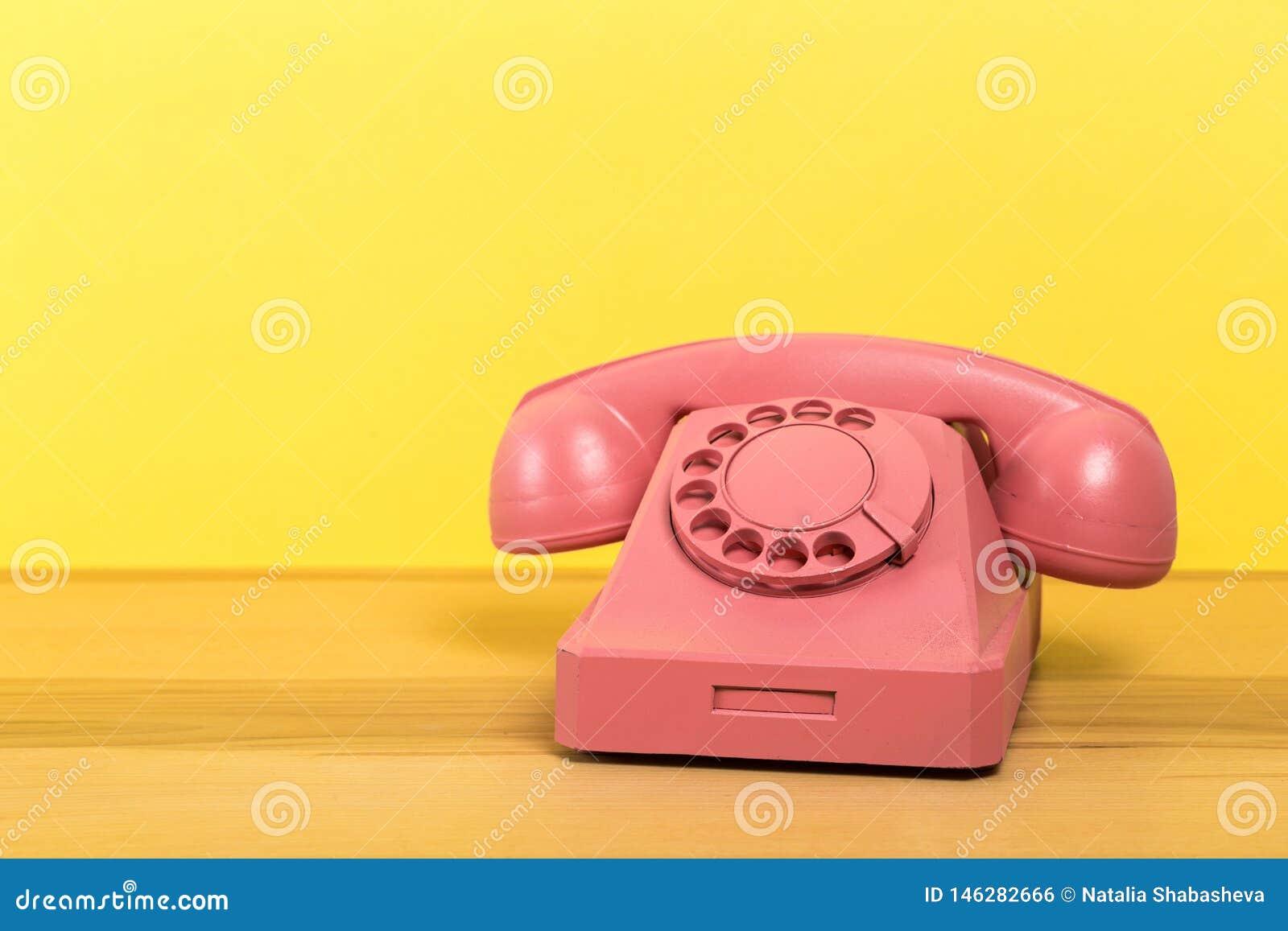 Rosa telefon f?r tappning p? tr?tabellen med f?rgv?ggbakgrund