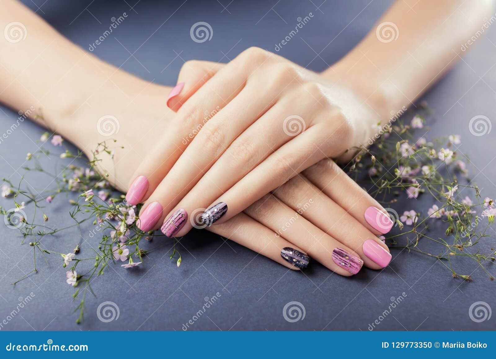 Rosa und schwarze Maniküre mit Blumen auf grauem Hintergrund Nageln Sie Kunst
