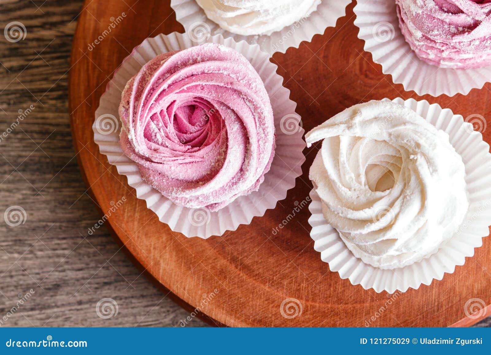 Rosa und weiße Eibische auf einem runden hölzernen Brett